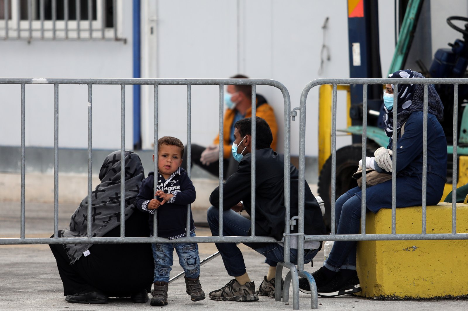 A boy looks through a metal barrier as migrants from the Moria camp wait to board a ferry that will transfer them to the mainland as a precaution against the coronavirus spread, on the island of Lesbos, Greece, May 3, 2020. (Reuters Photo)