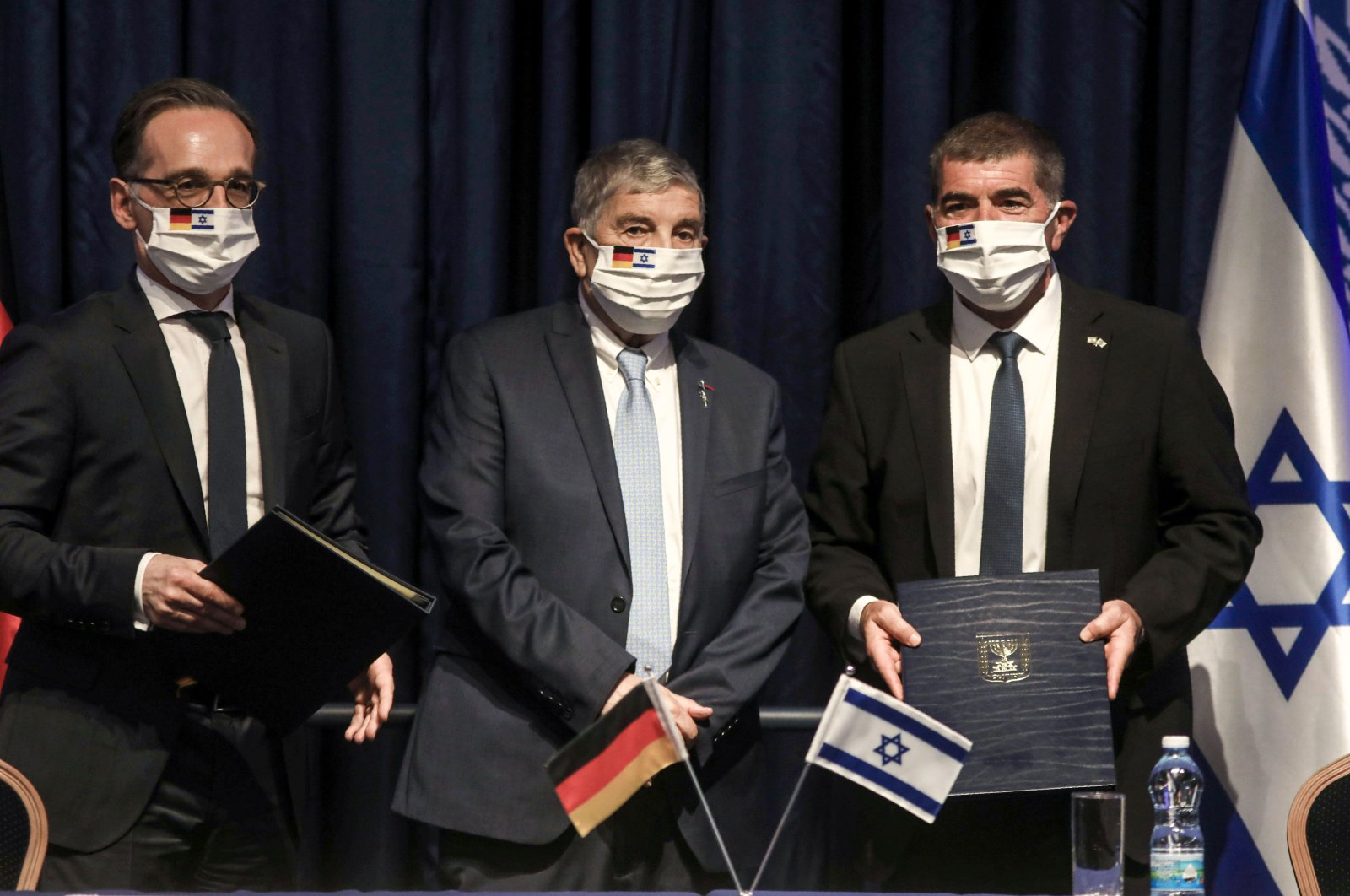 German Foreign Minister Heiko Maas (L), chairman of the Yad Vashem Holocaust Remembrance Center Avner Shalev (C) and Israeli Foreign Minister Gabi Ashkenazi (R) pose for a picture together after signing an agreement at the ministry headquarters in Jerusalem, Israel, June 10, 2020. (AFP Photo)