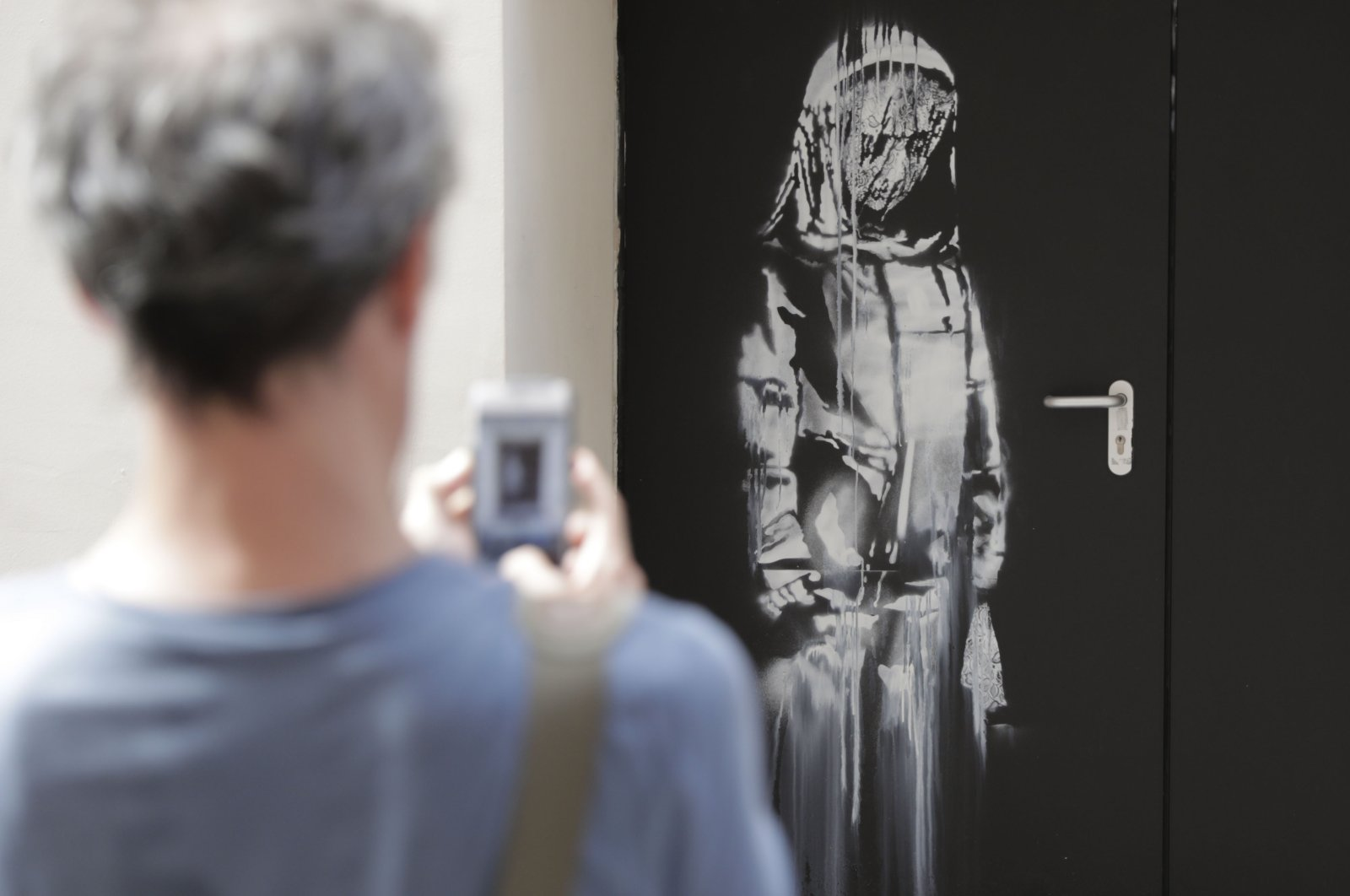 In this file photo taken on June 25, 2018, a man takes a photograph of an artwork by street artist Banksy in Paris on a side street to the Bataclan concert hall where a terrorist attack killed 90 people, November 13, 2015. (Photo by Thomas SAMSON via AFP)