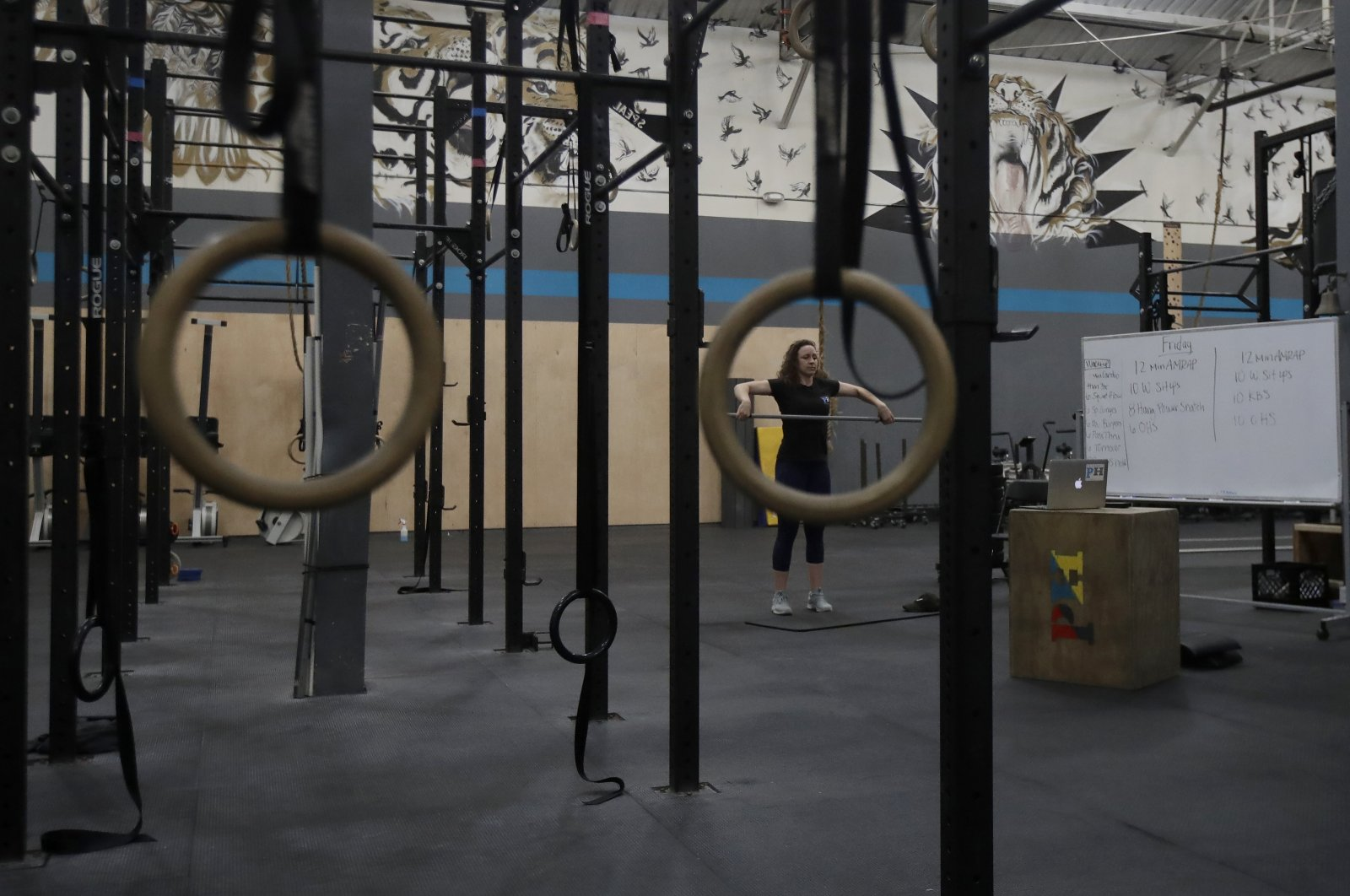 Alexis Garrod, CrossFit Potrero Hill partner and head coach, demonstrates an exercise to participants while instructing a class over Zoom in an empty gym in San Francisco, U.S., April 24, 2020. (AP Photo)