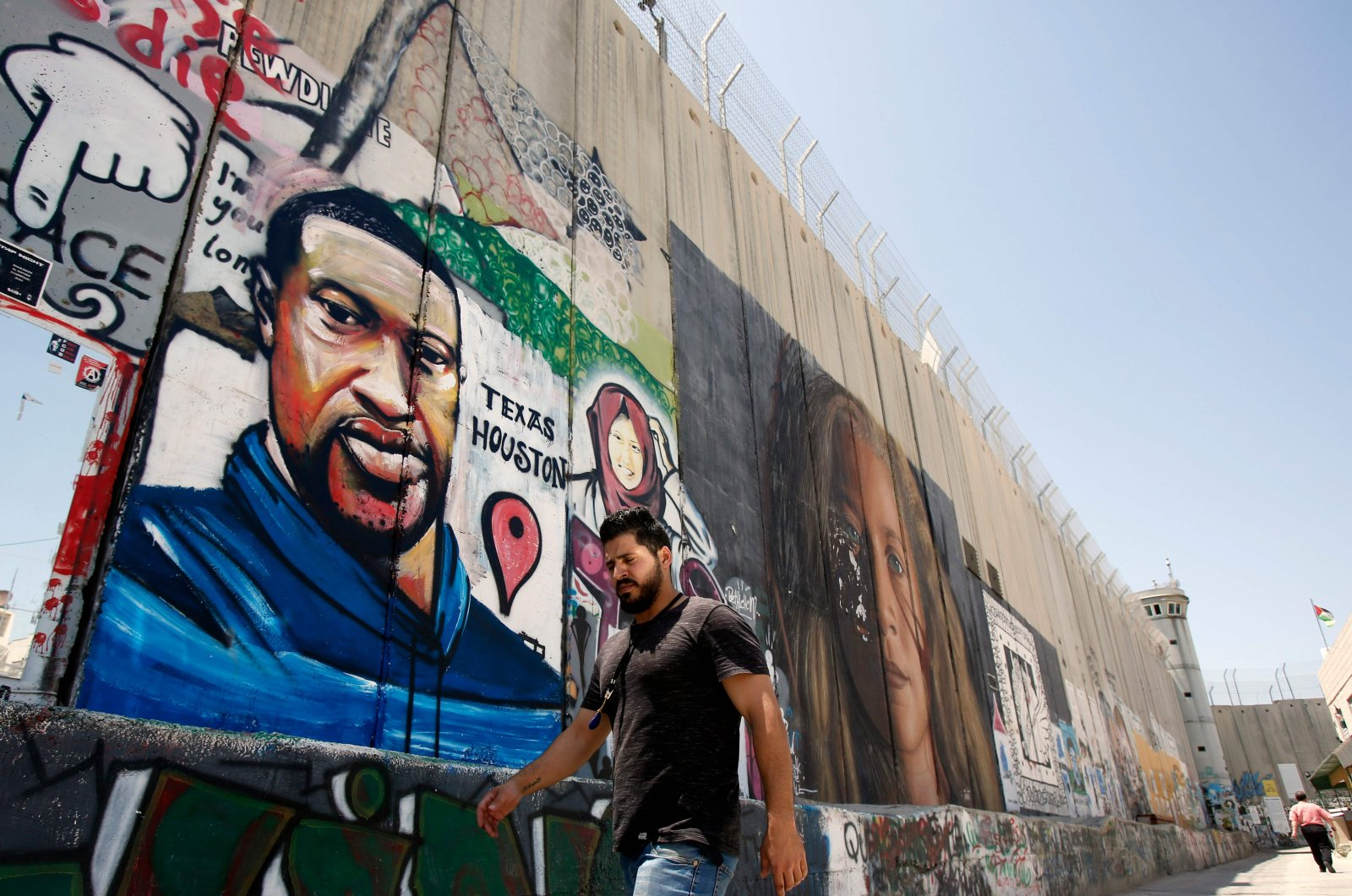 A Palestinian man walks past graffiti of George Floyd, an unarmed black man who died after a white policeman knelt on his neck during an arrest in the U.S., painted on a section of Israel's controversial separation barrier in the city of Bethlehem in the occupied West Bank, June 7, 2020. (AFP Photo)