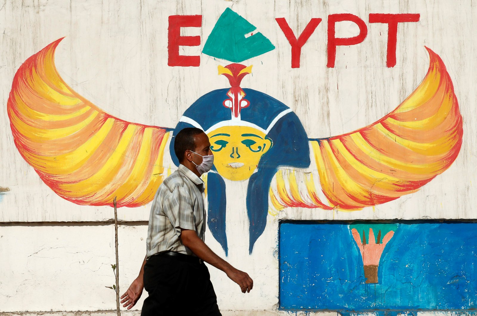A man wearing a protective face mask walks next to a wall with pharaonic images painted on it, Cairo, June 4, 2020. (REUTERS Photo)