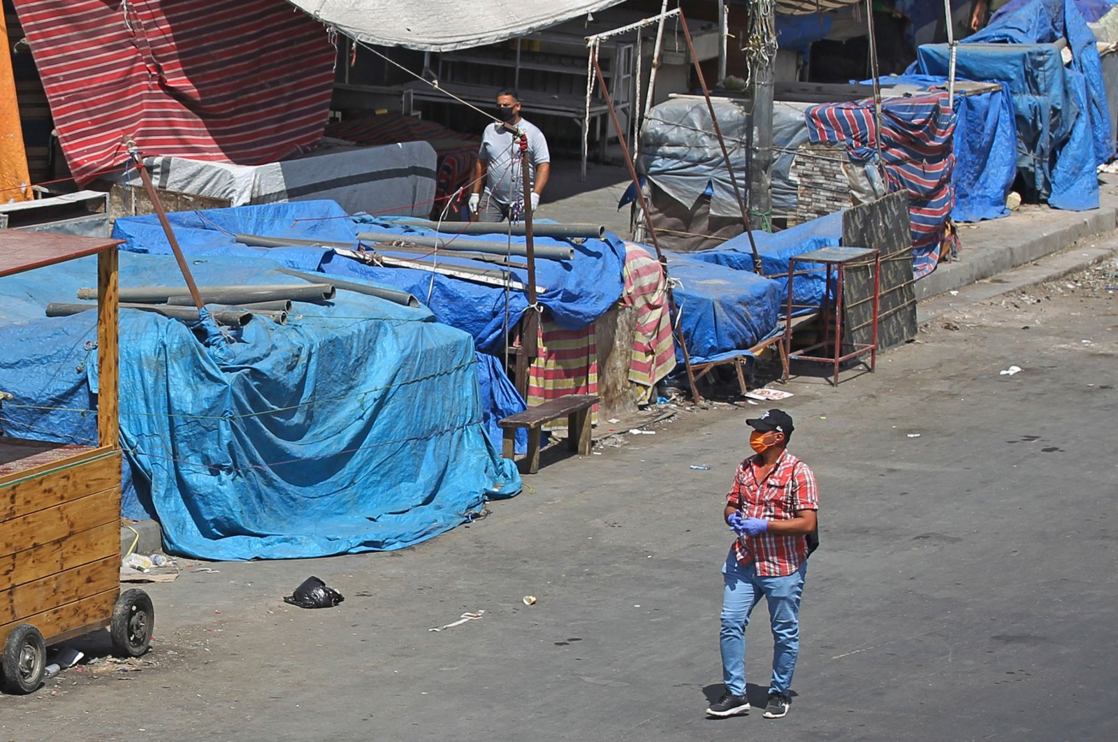 Mask-clad men walk by covered stalls amid an extended curfew, Baghdad, June 8, 2020. (AFP Photo)
