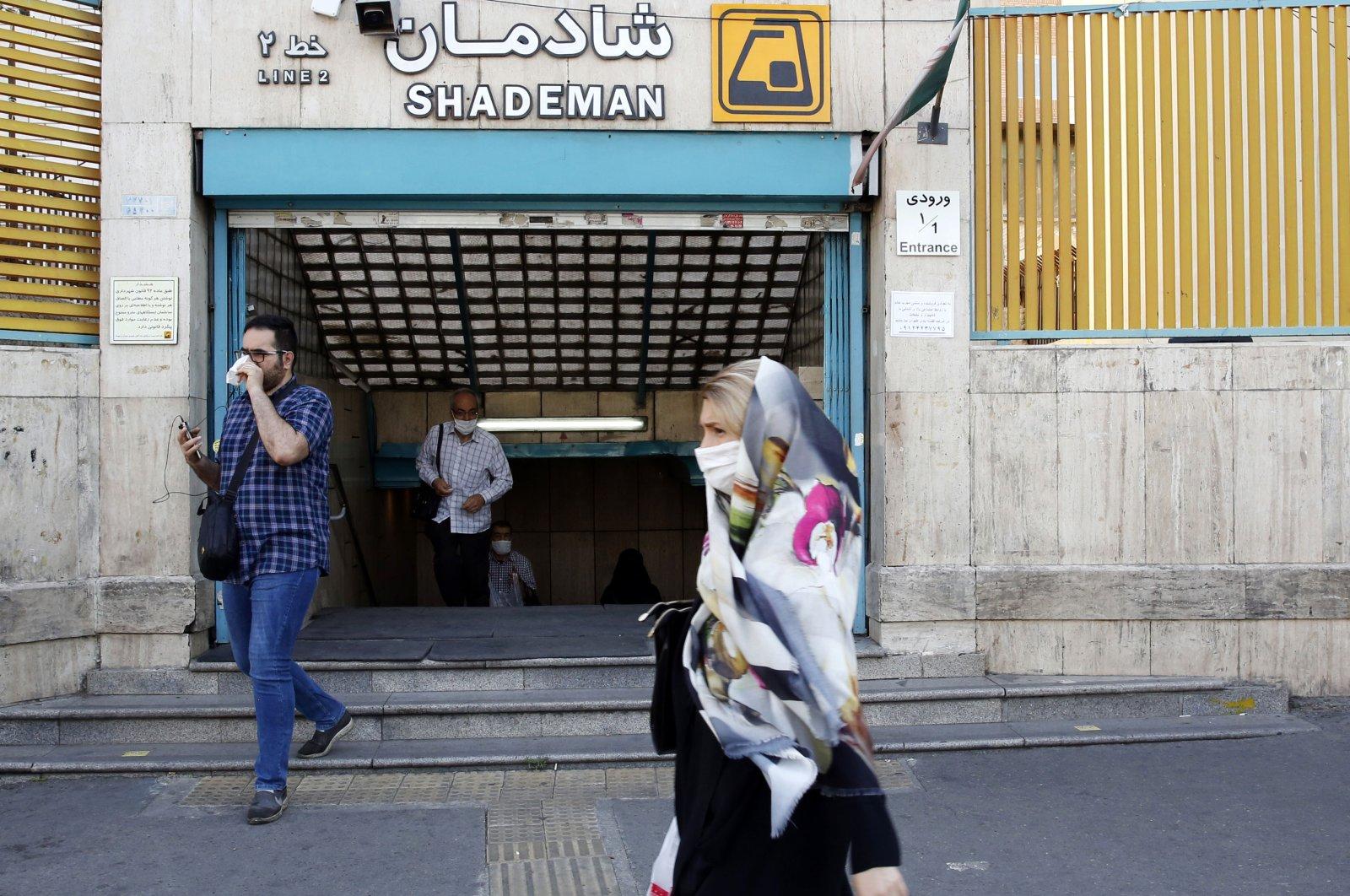 An Iranian woman wearing a face mask walks past a metro station, Tehran, June 10, 2020. (AFP Photo)