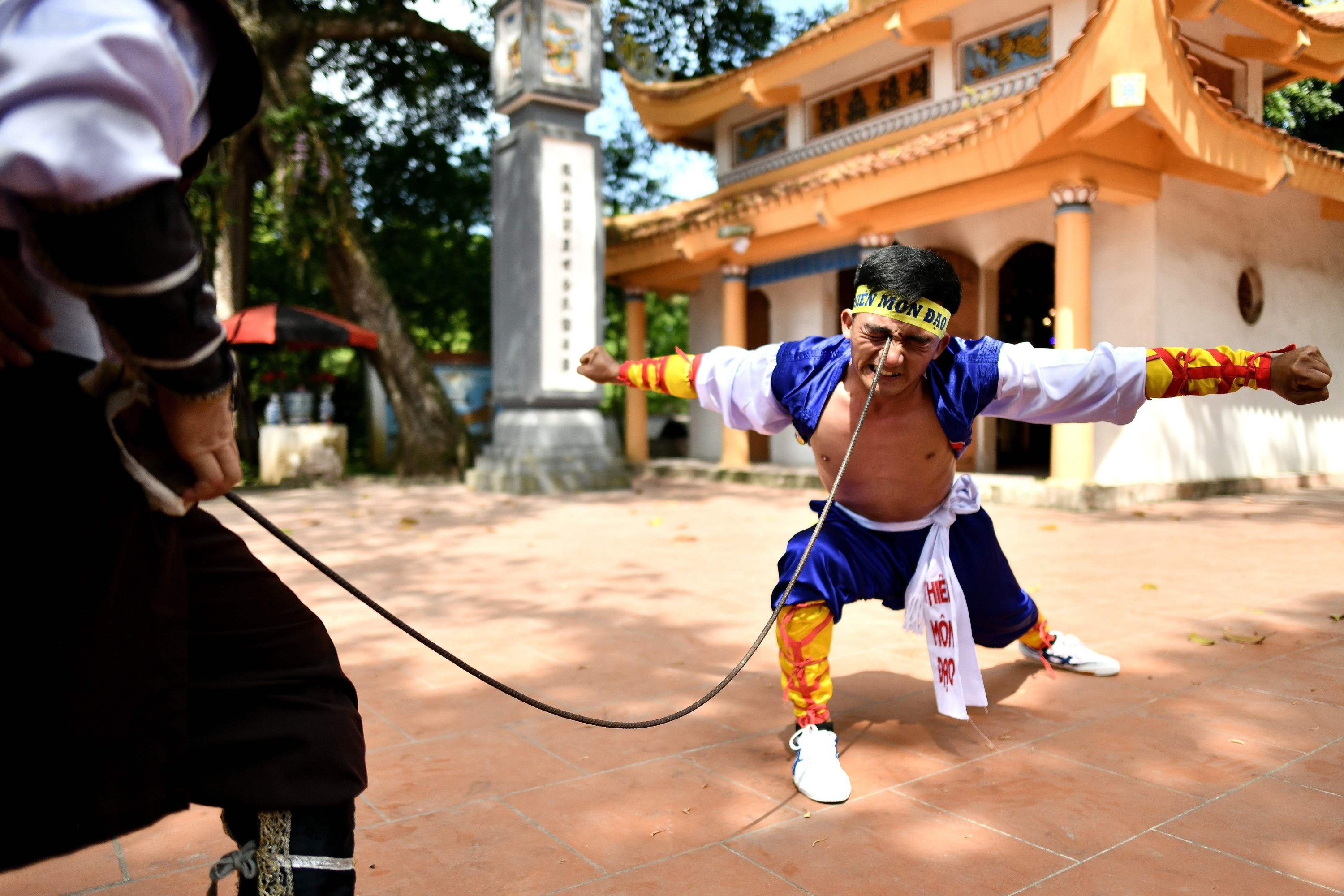 Le Van Thang, 28, student of the centuries-old martial art of Thien Mon Dao, bends a construction rebar against his eye socket inside the Bach Linh temple compound at Du Xa Thuong village in Hanoi, Vietnam, June 7, 2020. (AFP Photo)