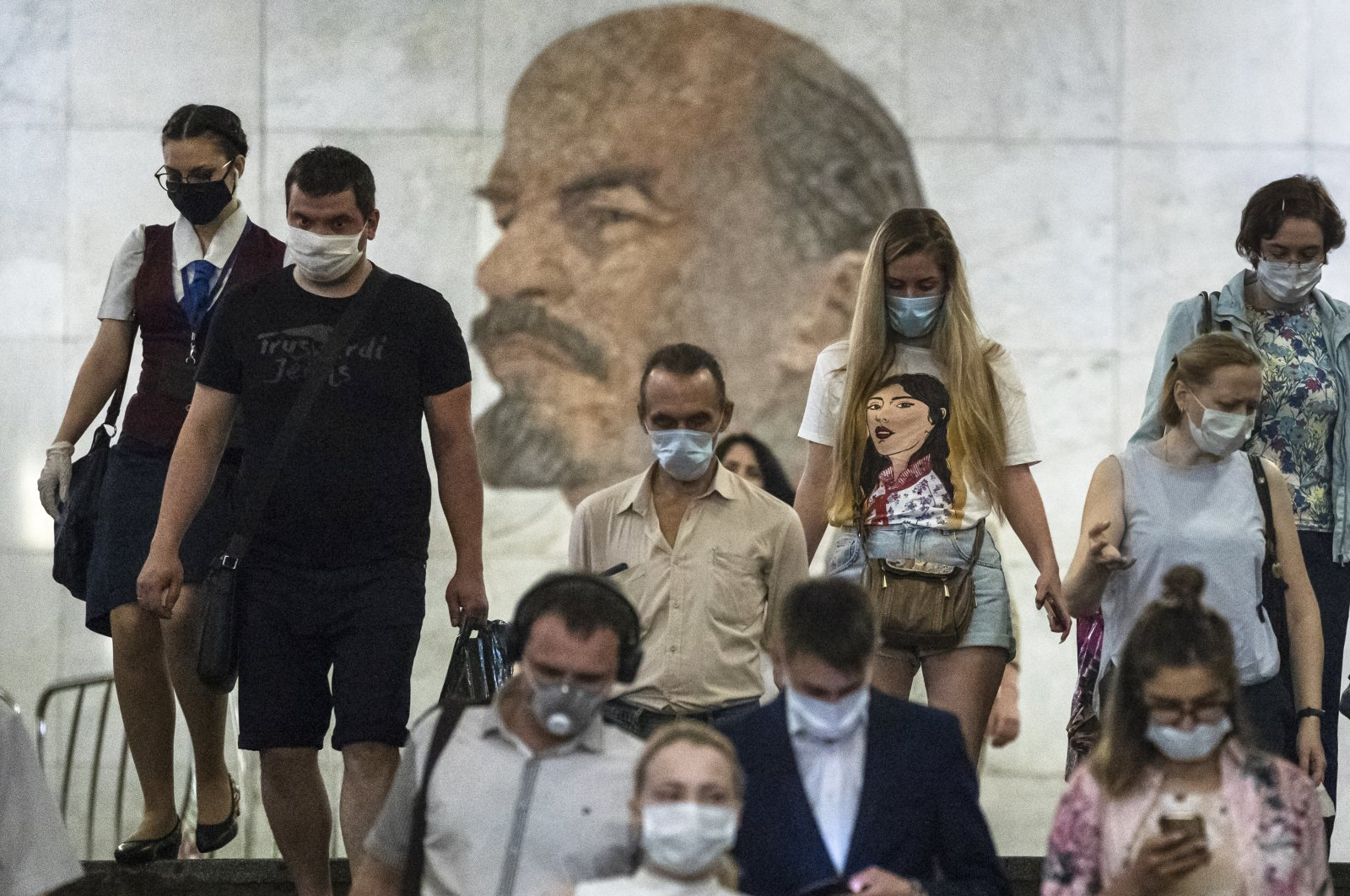 People wearing face masks to protect against coronavirus walk through the subway, with a portrait of Soviet founder Vladimir Lenin in the background, in Moscow, Russia, June 10, 2020. (AP Photo)