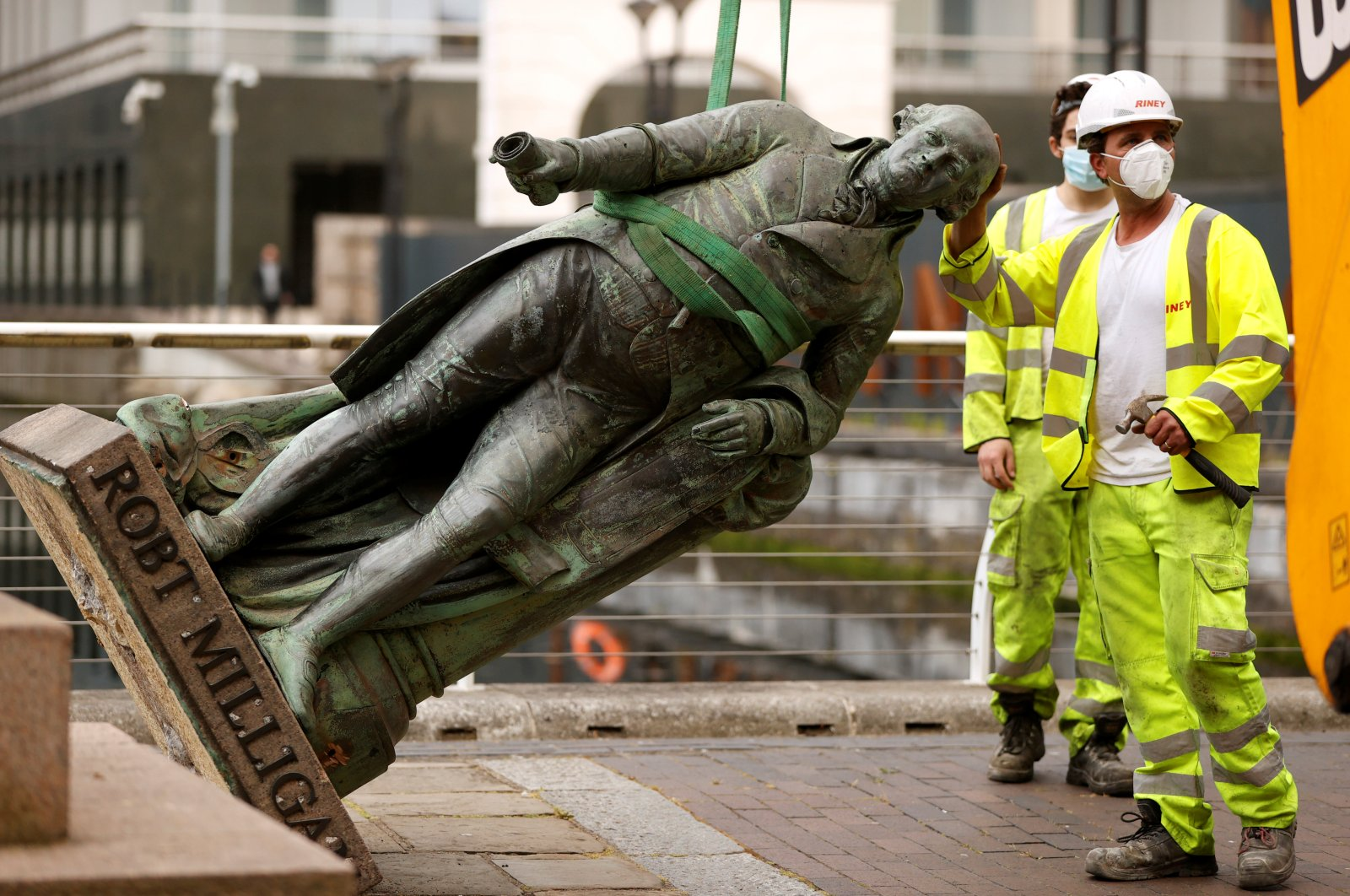 A statue of Robert Milligan is removed by workers outside the Museum of London Docklands near Canary Wharf, following the death of George Floyd, London, June 9, 2020. (Reuters Photo)
