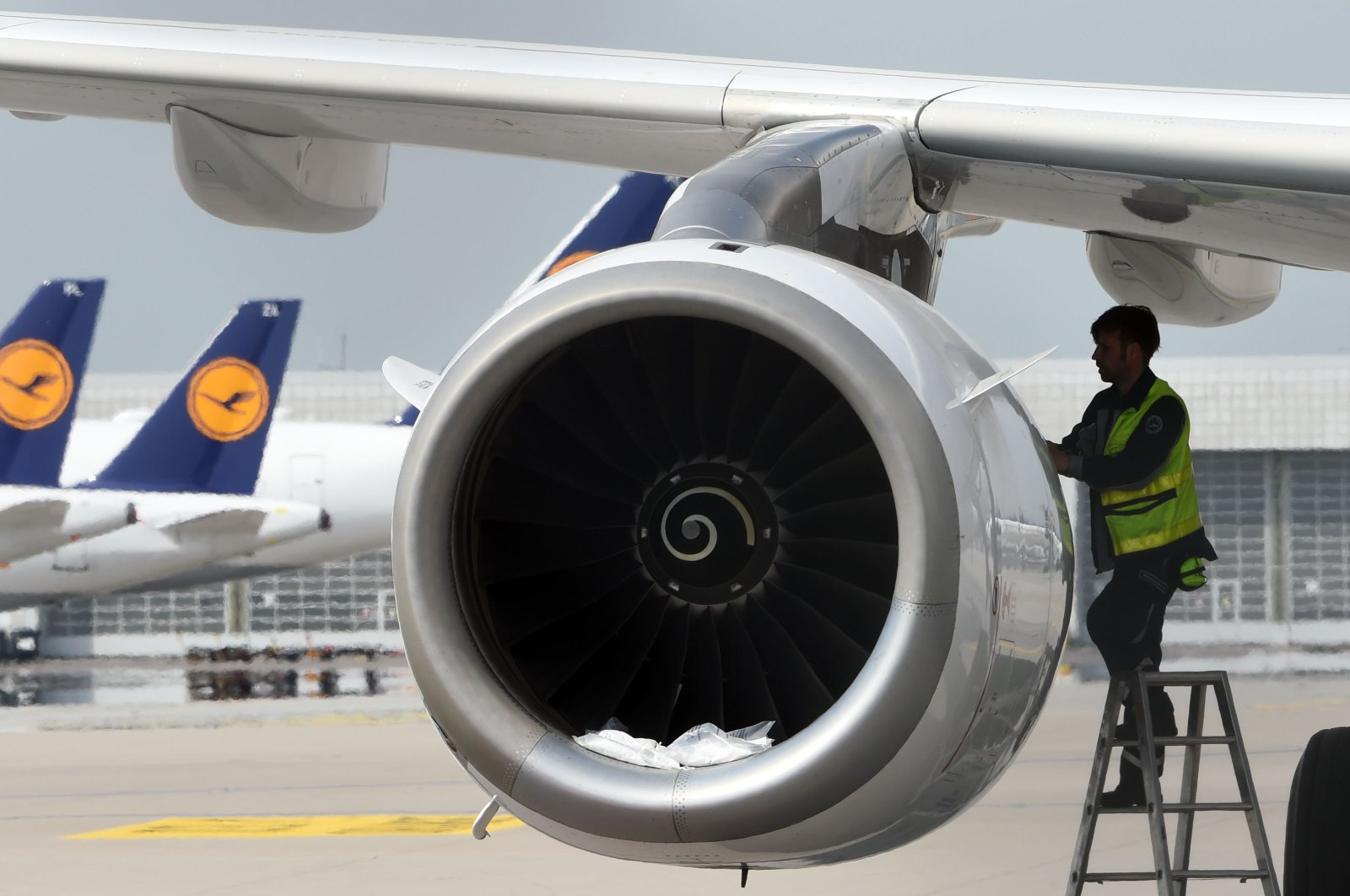 A technician of the German airline Lufthansa works on a parked plane at Munich International Airport, Munich, southern Germany, April 28, 2020. (AFP Photo)