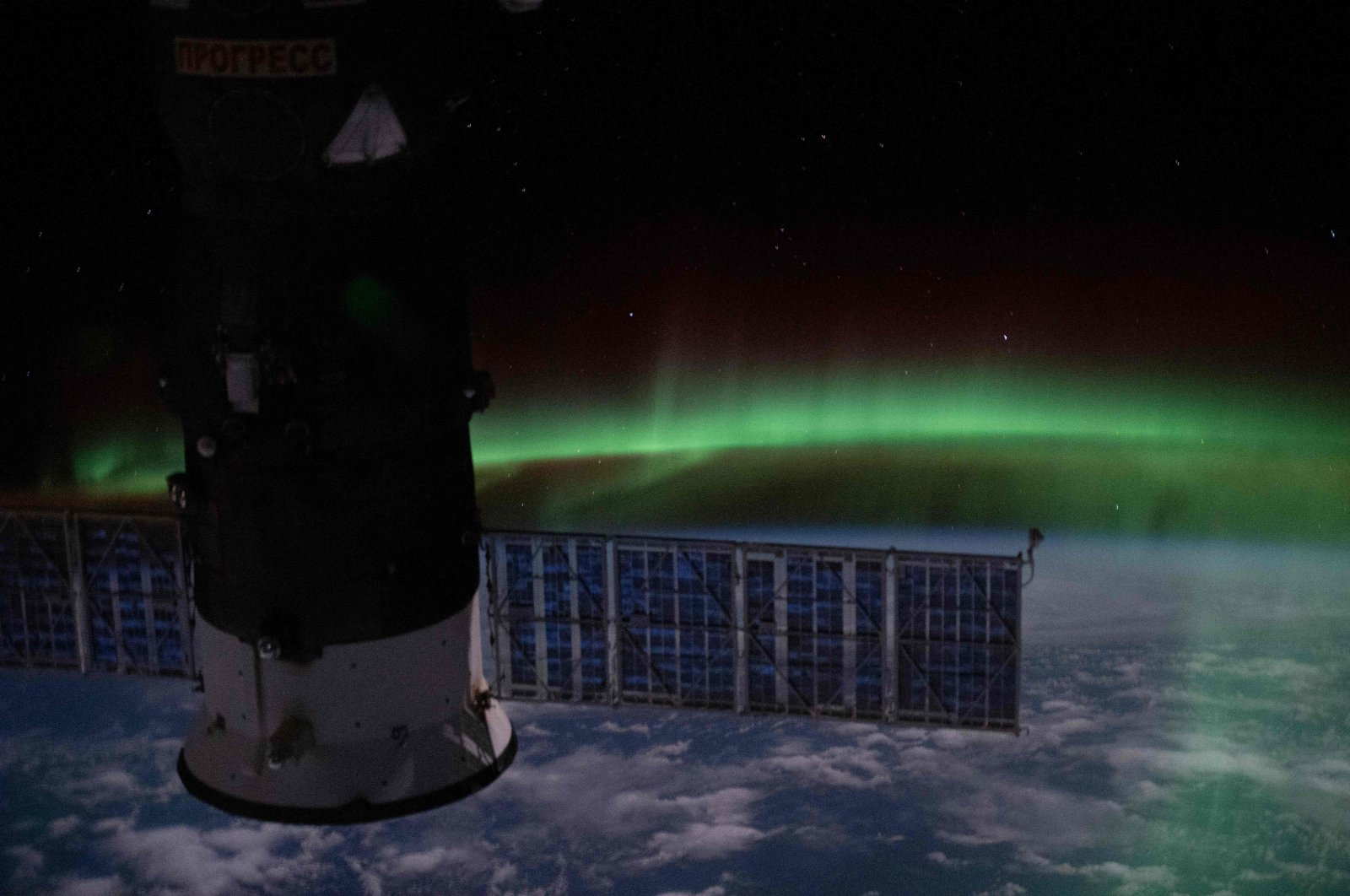 """This handout photo released June 10, 2020, shows an orbital nighttime view from the International Space Station as it orbits above the Indian Ocean with the """"aurora australis"""" and a starry sky with Russia's Progress 74 resupply ship in the foreground on June 7, 2020. (NASA via AFP)"""