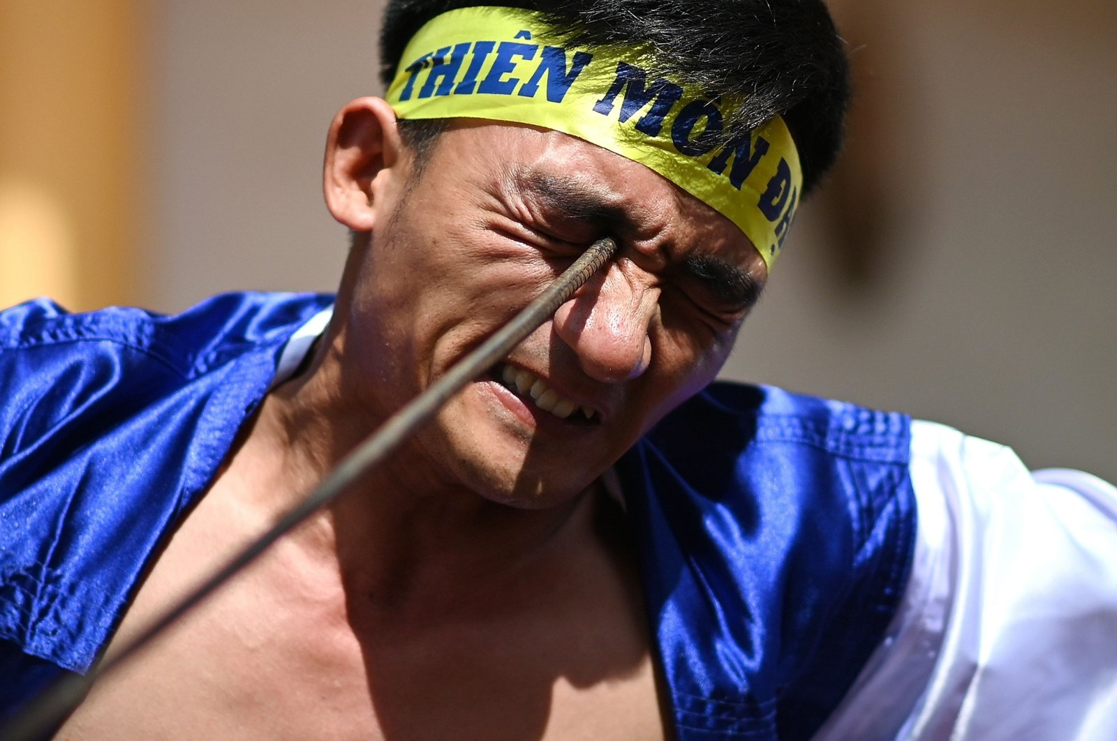Le Van Thang, 28, a student of the centuries-old martial art of Thien Mon Dao, bends a construction rebar against his eye socket inside the Bach Linh temple compound at Du Xa Thuong village in Hanoi, Vietnam, June 7, 2020. (AFP Photo)