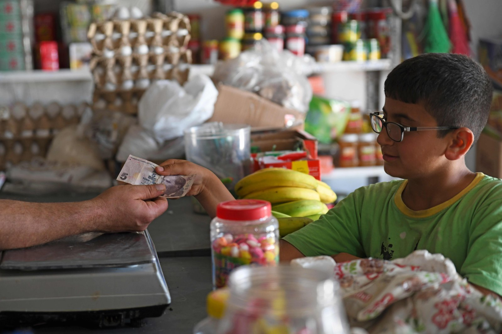 A boy pays a merchant with a Turkish lira banknote at a shop in the town of Jinderes, in the Afrin district of northwestern Syria, June 10, 2020. (AFP Photo)