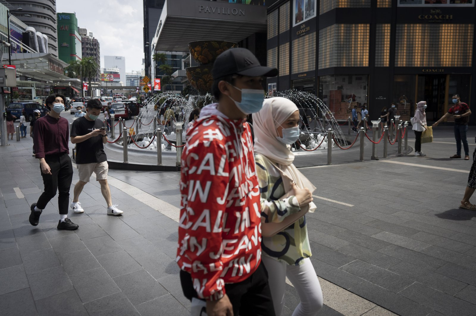 Shoppers wearing face masks walk at a shopping mall in downtown Kuala Lumpur, Malaysia, June 7, 2020. The Malaysian government has lifted the conditional movement order (CMCO) and replaced it with a recovery movement control order effective June 10 until Aug. 31. (AP Photo)