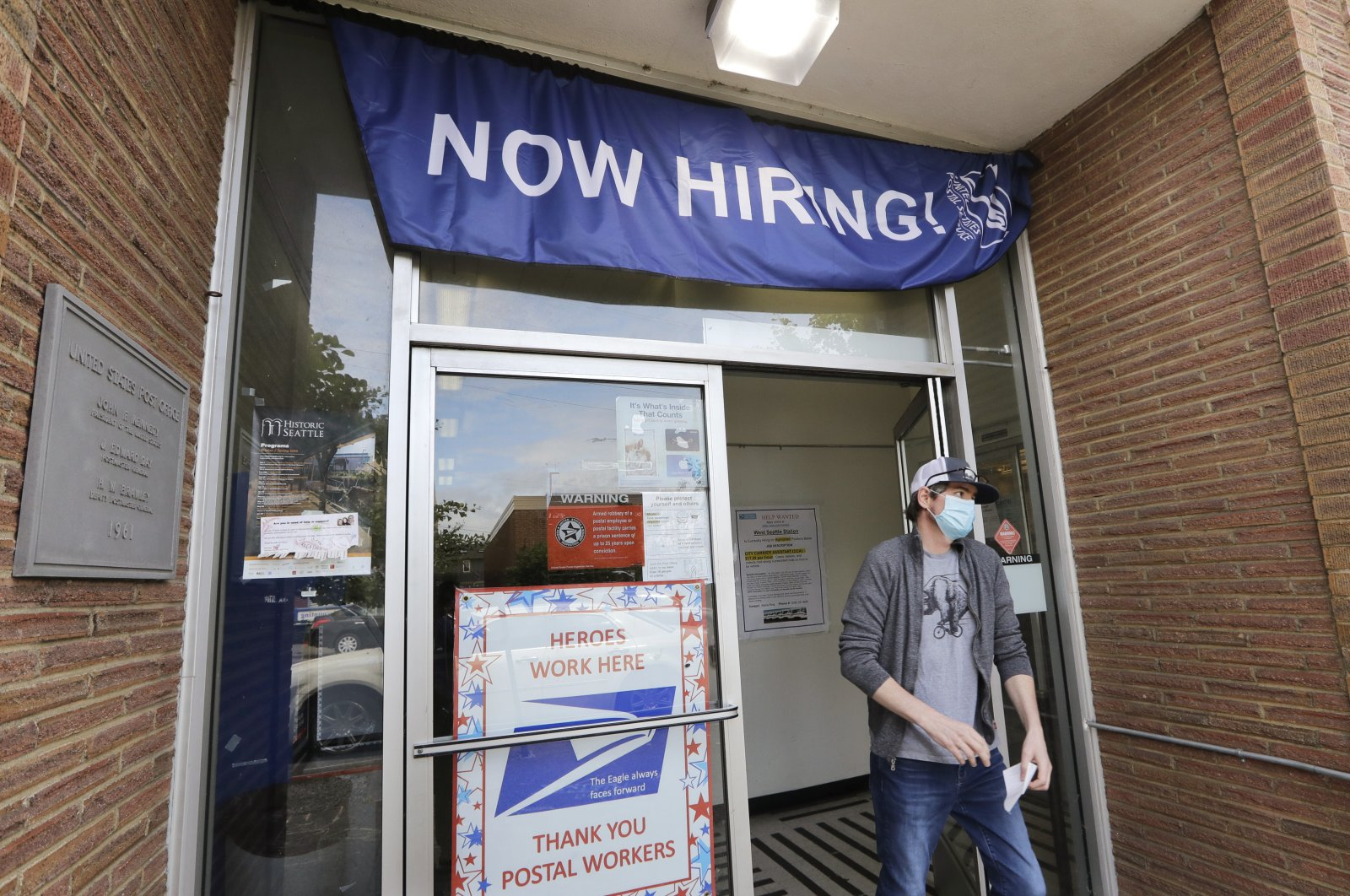 A customer walks out of a U.S. Post Office branch and under a banner advertising a job opening, in Seattle, June 4, 2020. (AP Photo)