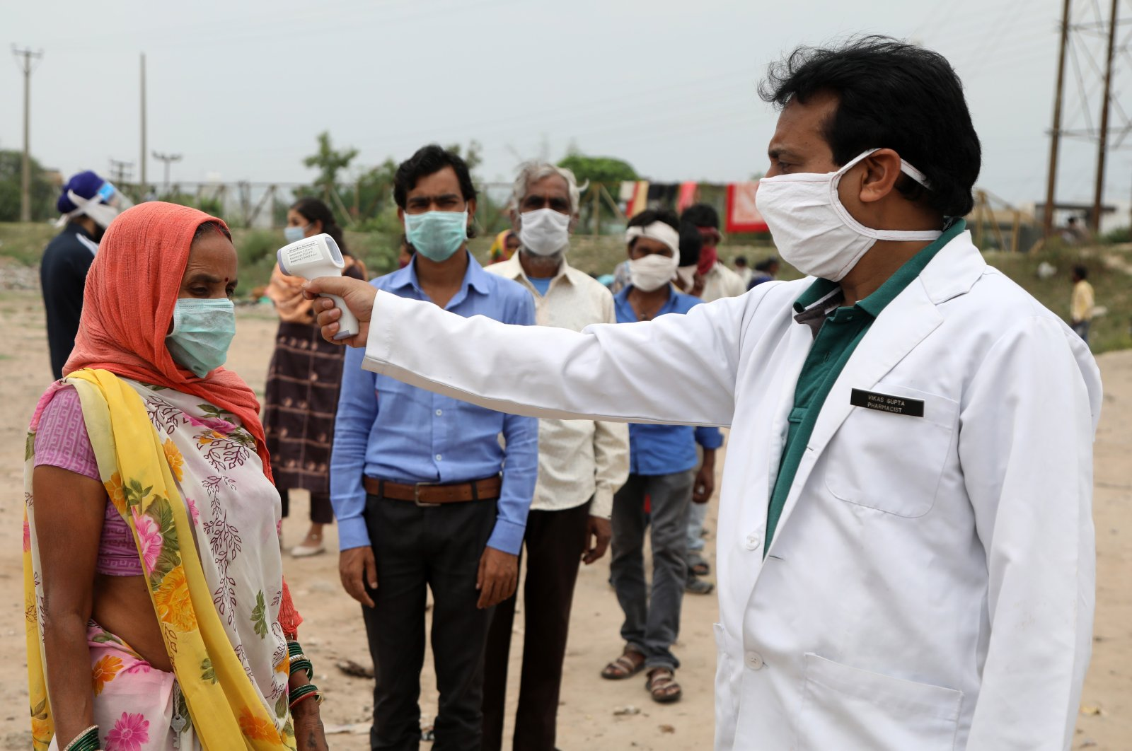 A health worker checks the body temperature of migrant laborers from Chhattisgarh state before sending them to their hometowns after they were stranded in an open area, in Jammu, India, June 11, 2020. (EPA Photo)