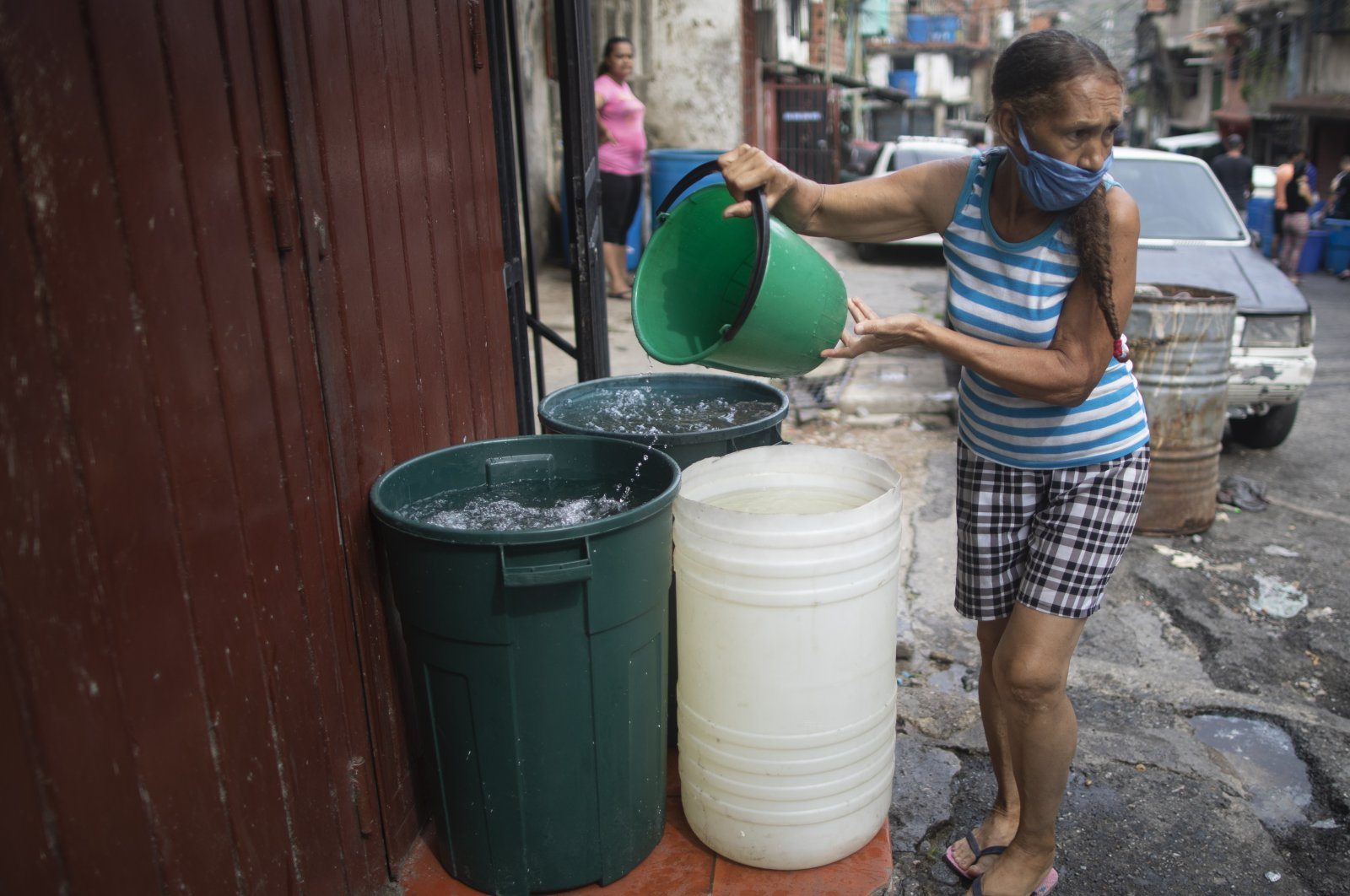 A woman, wearing a protective face mask as a measure to help curb the spread of the coronavirus, fills a big container with water provided by a government water truck, in the Petare slum of Caracas, June 10, 2020. (AP)