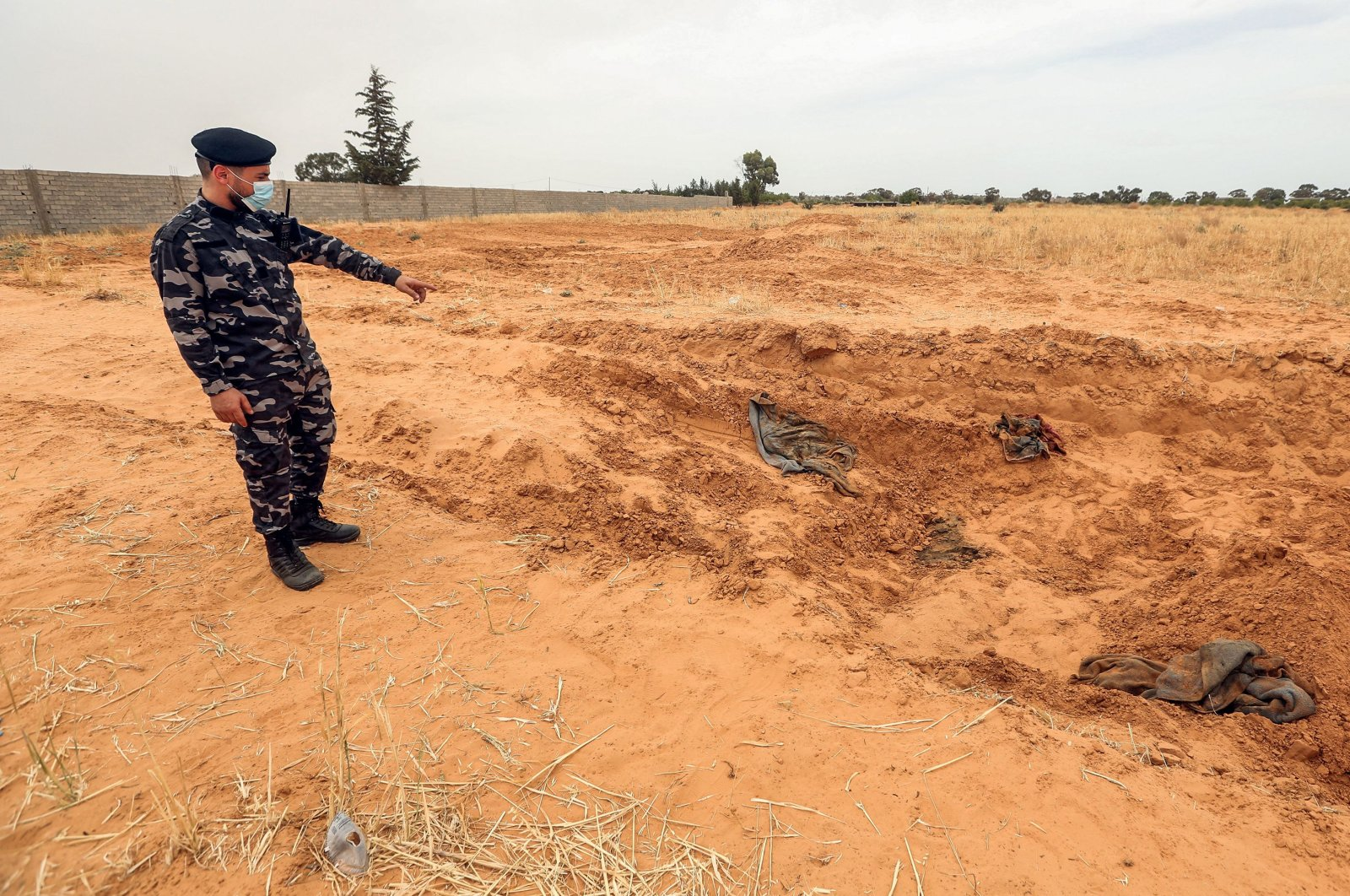 A member of security forces affiliated with the Libyan Government of National Accord (GNA)'s Interior Ministry stands at the reported site of a mass grave in the town of Tarhuna, June 11, 2020. (AFP Photo)
