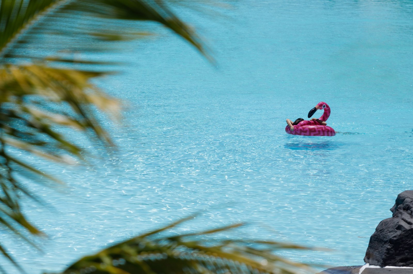 A girl enjoys a warm day atop a pink flamingo pool float in a hotel swimming pool, in Santa Cruz de Tenerife, Canary Islands, Spain, May 26, 2020. (EPA Photo)