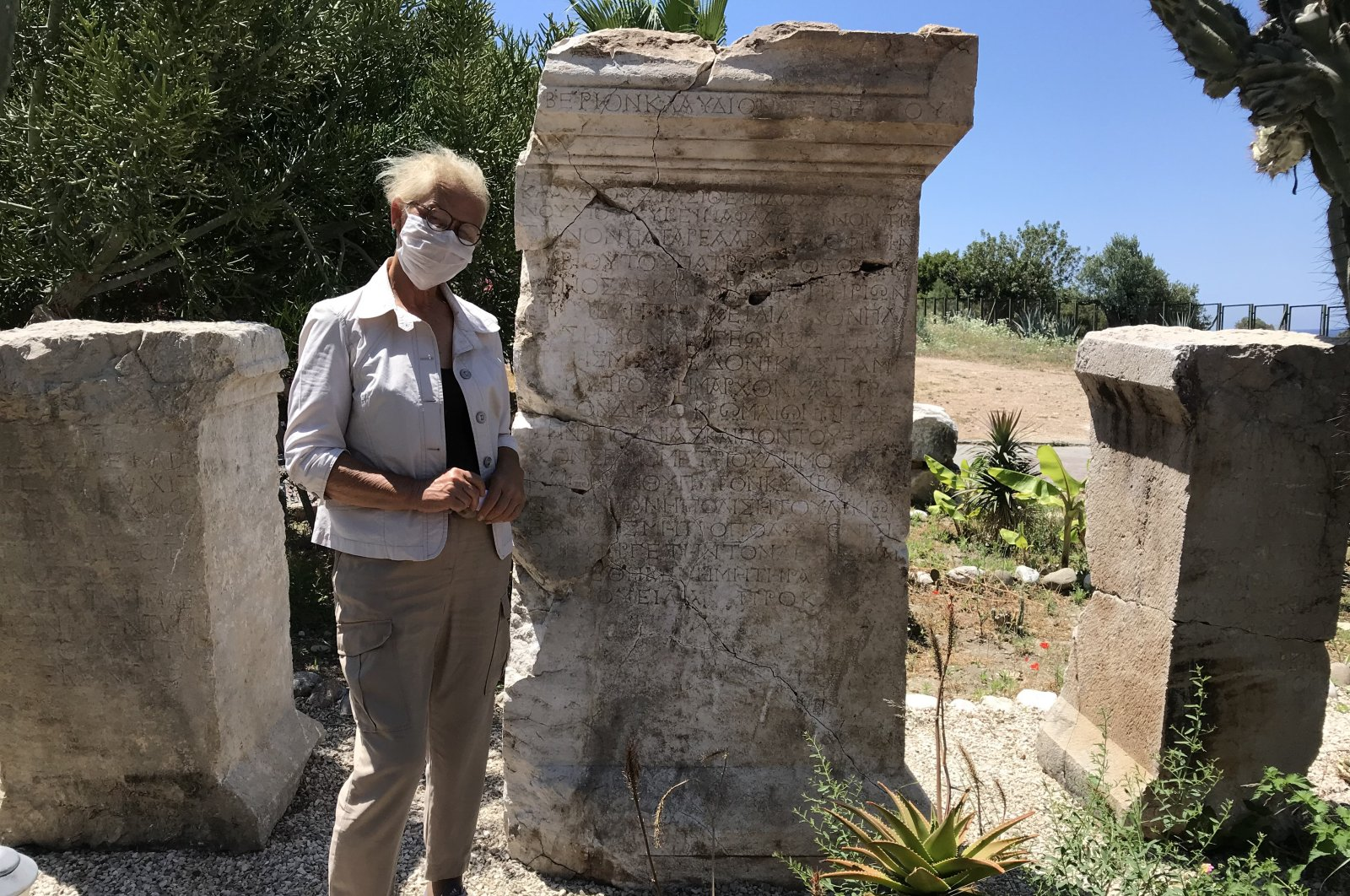Chief excavator Havva Işkan Işık poses next to the inscription. (AA PHOTO)