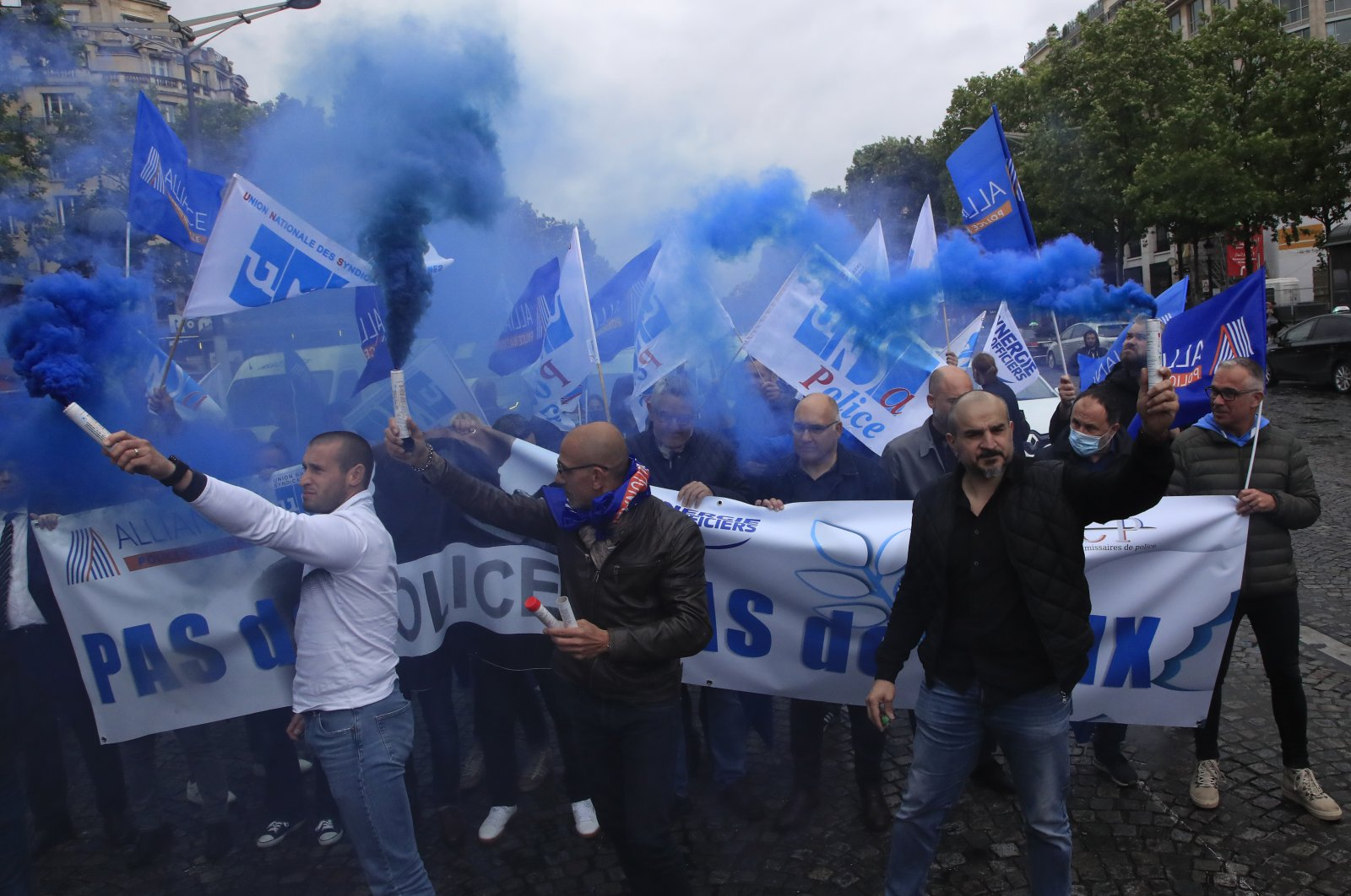 """French police unionists fire blue flares as they demonstrate with a banner reading"""" No police, no peace"""" down the Champs-Elysee avenue, Paris, June 12, 2020. (AP Photo)"""
