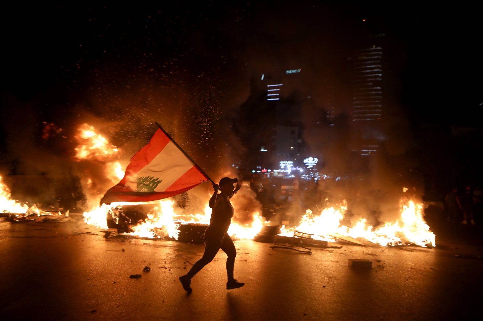 A protester holding the Lebanese flag runs as protesters block the Jounieh Tripoli highway with flaming tires, Beirut, Lebanon, June 11, 2020. (AFP Photo)
