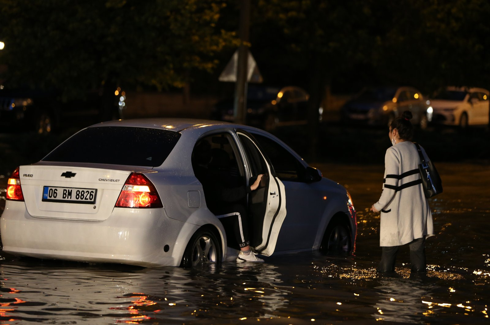 A woman walks in knee-high water as she tries to get inside a car, Ankara, Turkey, June 5, 2020. (AA Photo)