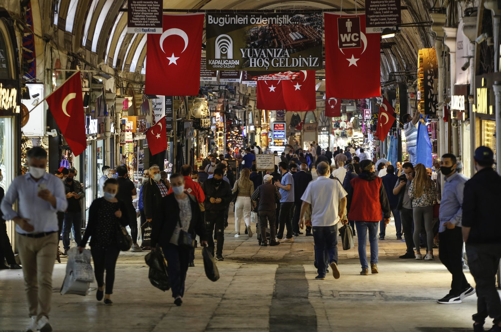 People, most wearing protective face masks for protection against the coronavirus, walk at the iconic Grand Bazaar in Istanbul, June 1, 2020. (AP Photo)