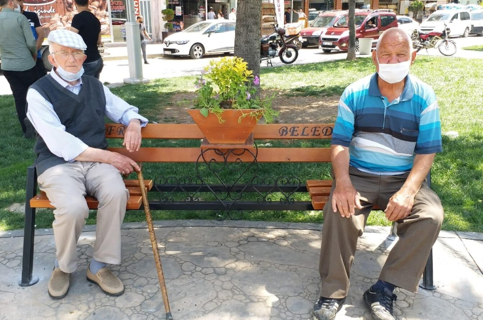 """Two men sit on a """"social distancing"""" bench in a park in Bafra district, in Samsun, Turkey, June 12, 2020. (İHA Photo)"""