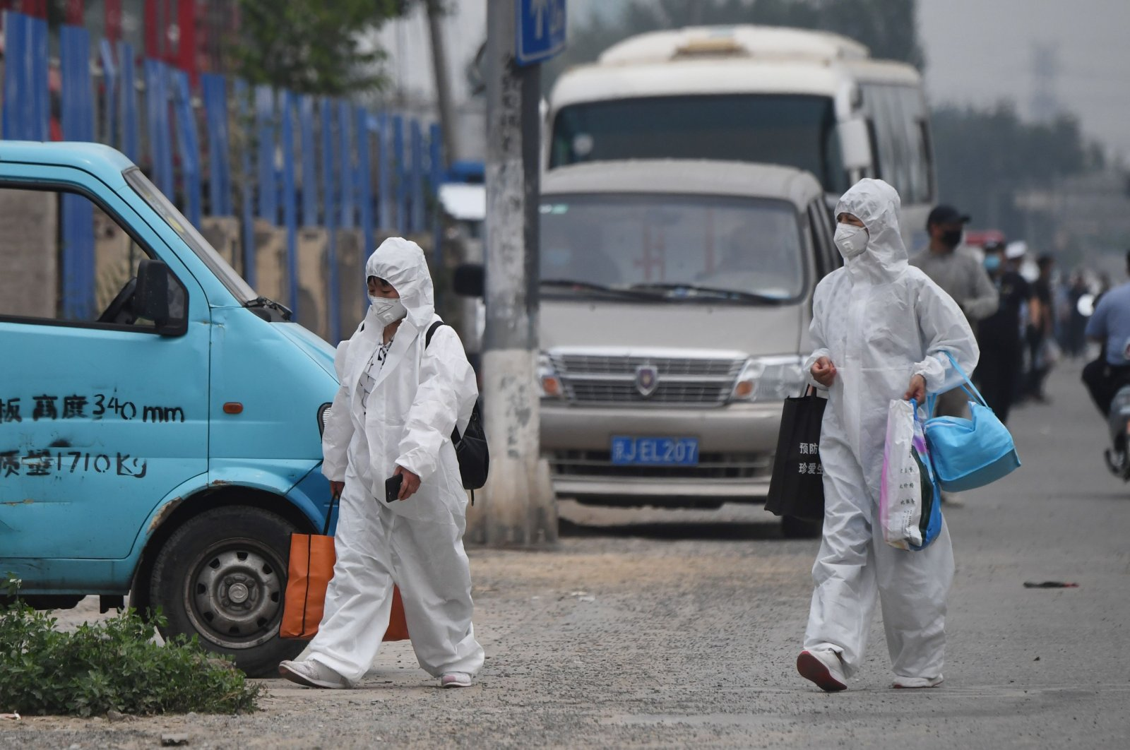 Two women wear protective suits as they walk on a street near the closed Xinfadi market in Beijing on June 13, 2020. (AFP Photo)