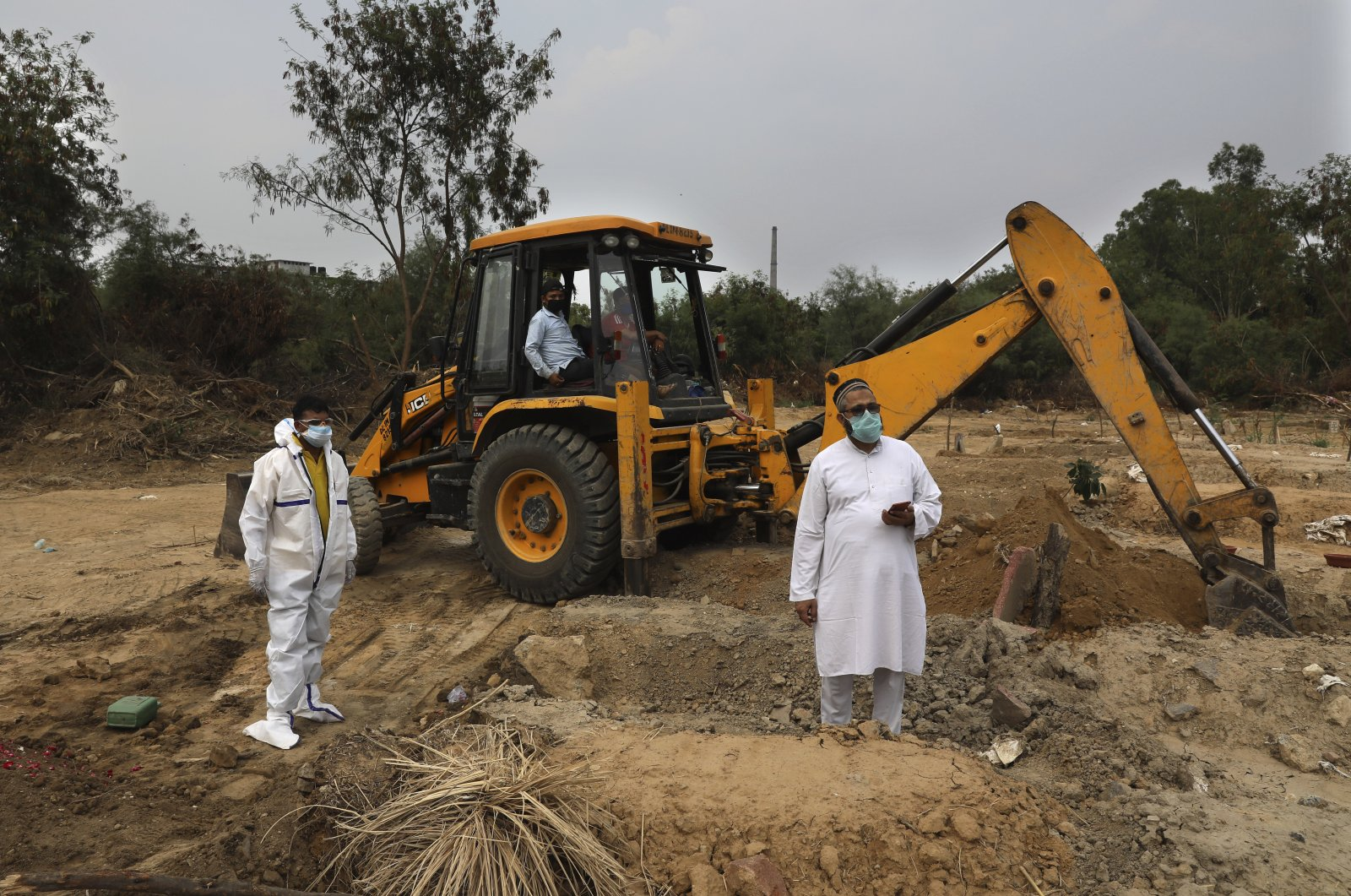 People wait for others to join as an earthmover digs a grave for the burial of a COVID-19 victim at a cemetery in New Delhi, India, June 5, 2020. (AP Photo)