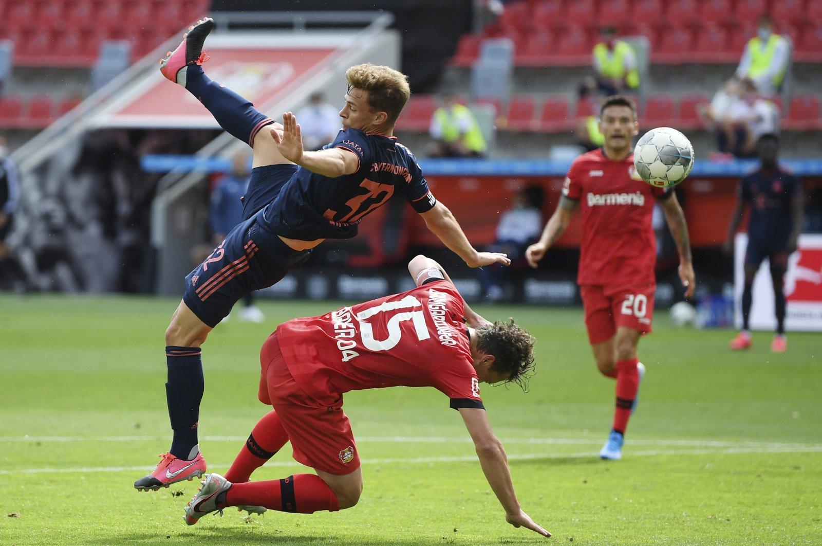 Joshua Kimmich (L) from Munich falls in a duel over Julian Baumgartlinger from Leverkusen during the German Bundesliga football match between Bayer Leverkusen and Bayern Munich in Leverkusen, Germany, June 6, 2020. (Pool via AP)