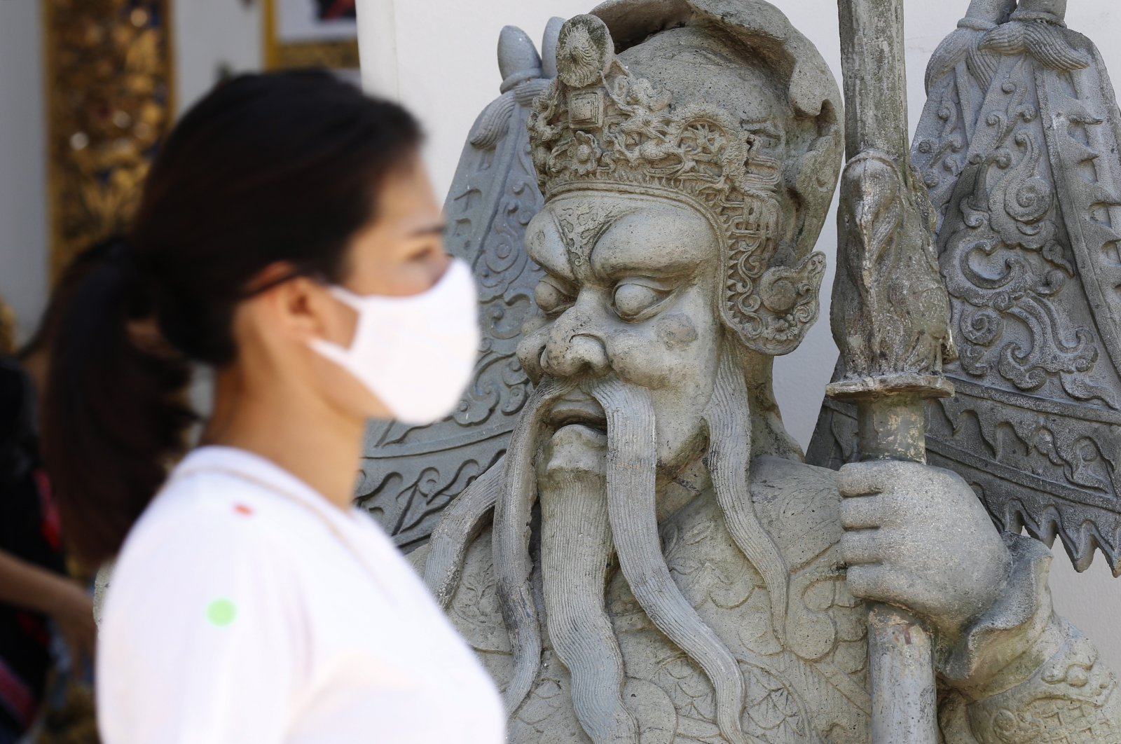 A Thai woman wears a face mask as she walks past a Chinese warrior statue inside Wat Pho temple in Bangkok, Thailand, June 13, 2020. (EPA Photo)