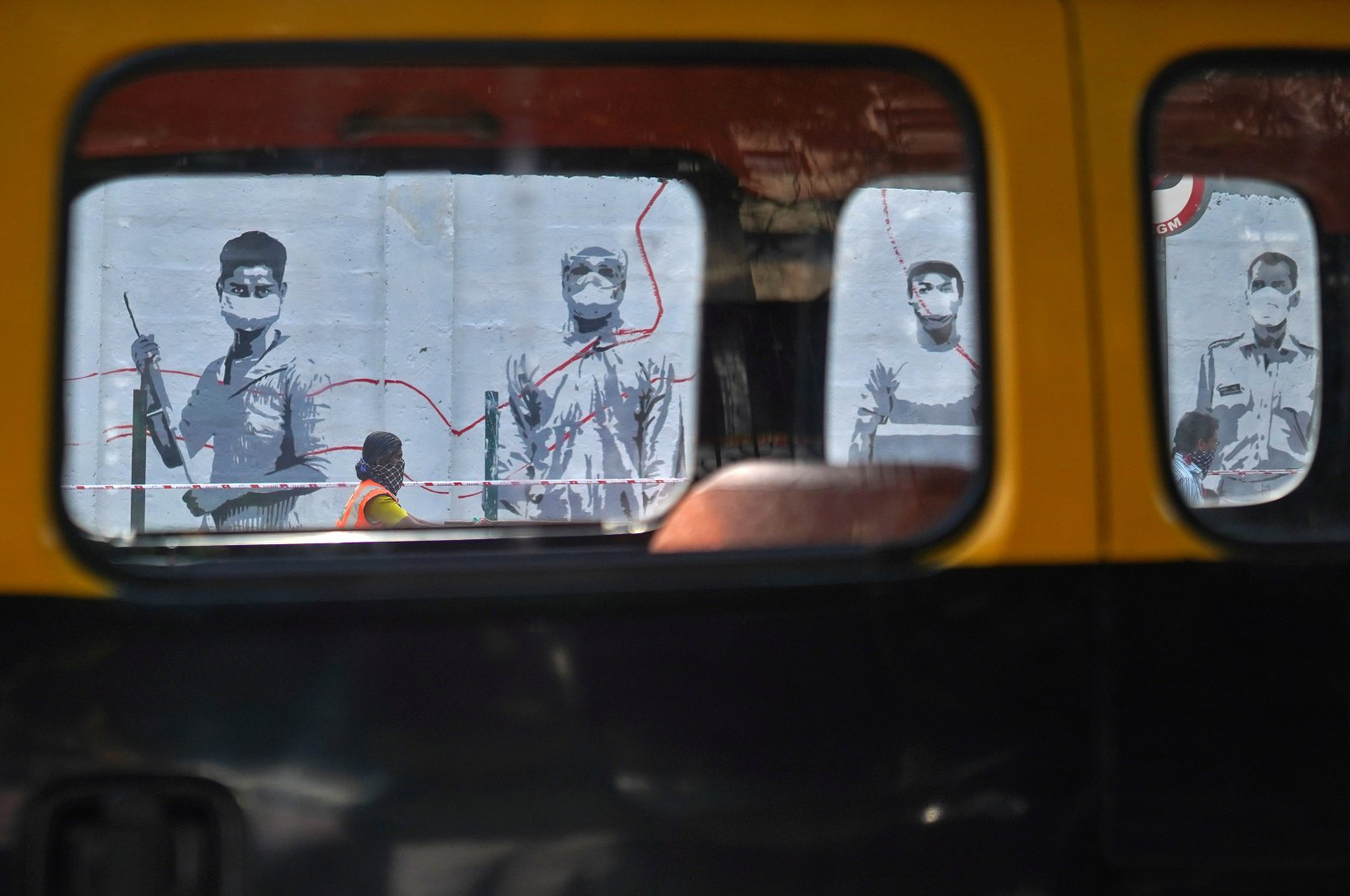 People wearing protective face masks are seen through the windows of a cab as they walk past a graffiti in Mumbai, India, June 12, 2020. (REUTERS Photo)