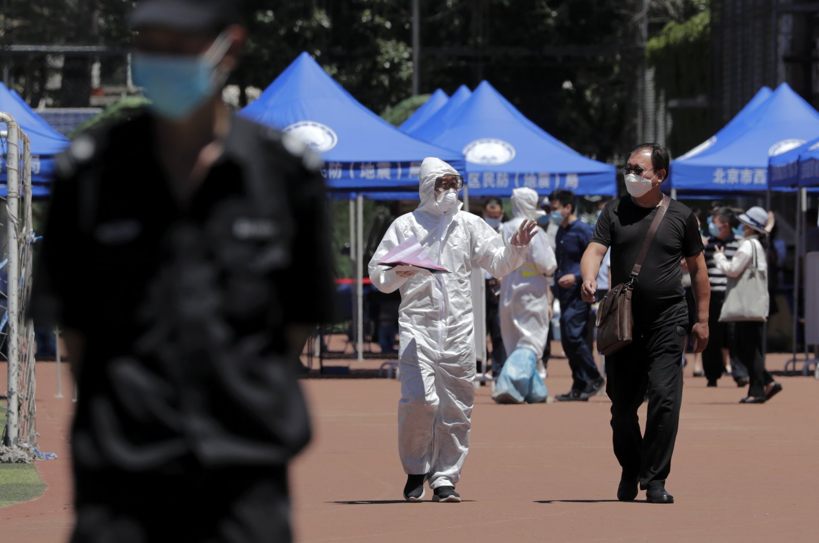 A worker in protective suit chats with a resident who was either living surrounding the Xinfadi wholesale market or have visited to the market to get a nucleic acid test at a stadium in Beijing, Sunday, June 14, 2020. (AP Photo)