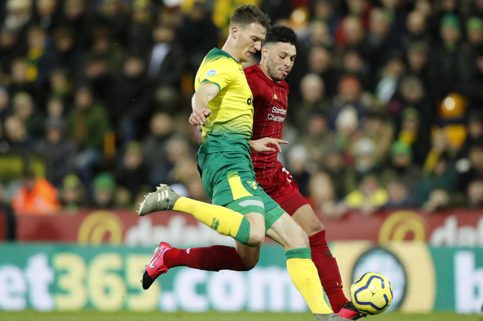 Norwich City's Max Aarons, front, duels for the ball with Liverpool's Alex Oxlade-Chamberlain during a Premier League match in Norwich, England, Feb. 15, 2020. (AP Photo)