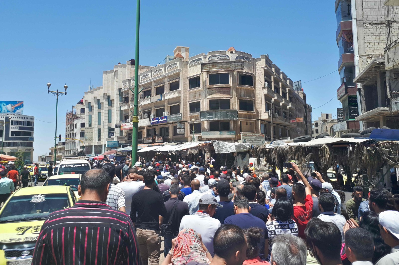 A handout picture released by the local news site Suwayda 24 shows Syrians chanting anti-regime slogans as they protest the country's deteriorating economic conditions and corruption, in the southern city of Suwaida, June 9, 2020. (SUWAYDA24 / AFP Photo)