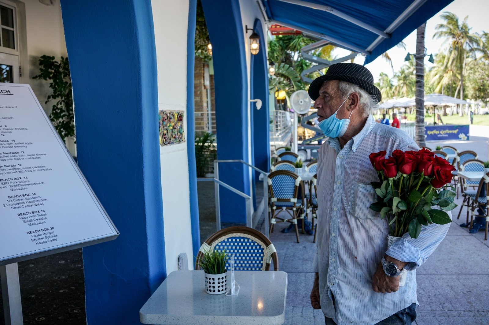 In this file photo taken on June 9, 2020, an elderly man holds a bouquet of roses as he looks at the menu outside a restaurant on Ocean Drive in South Beach, Miami. (AFP Photo)