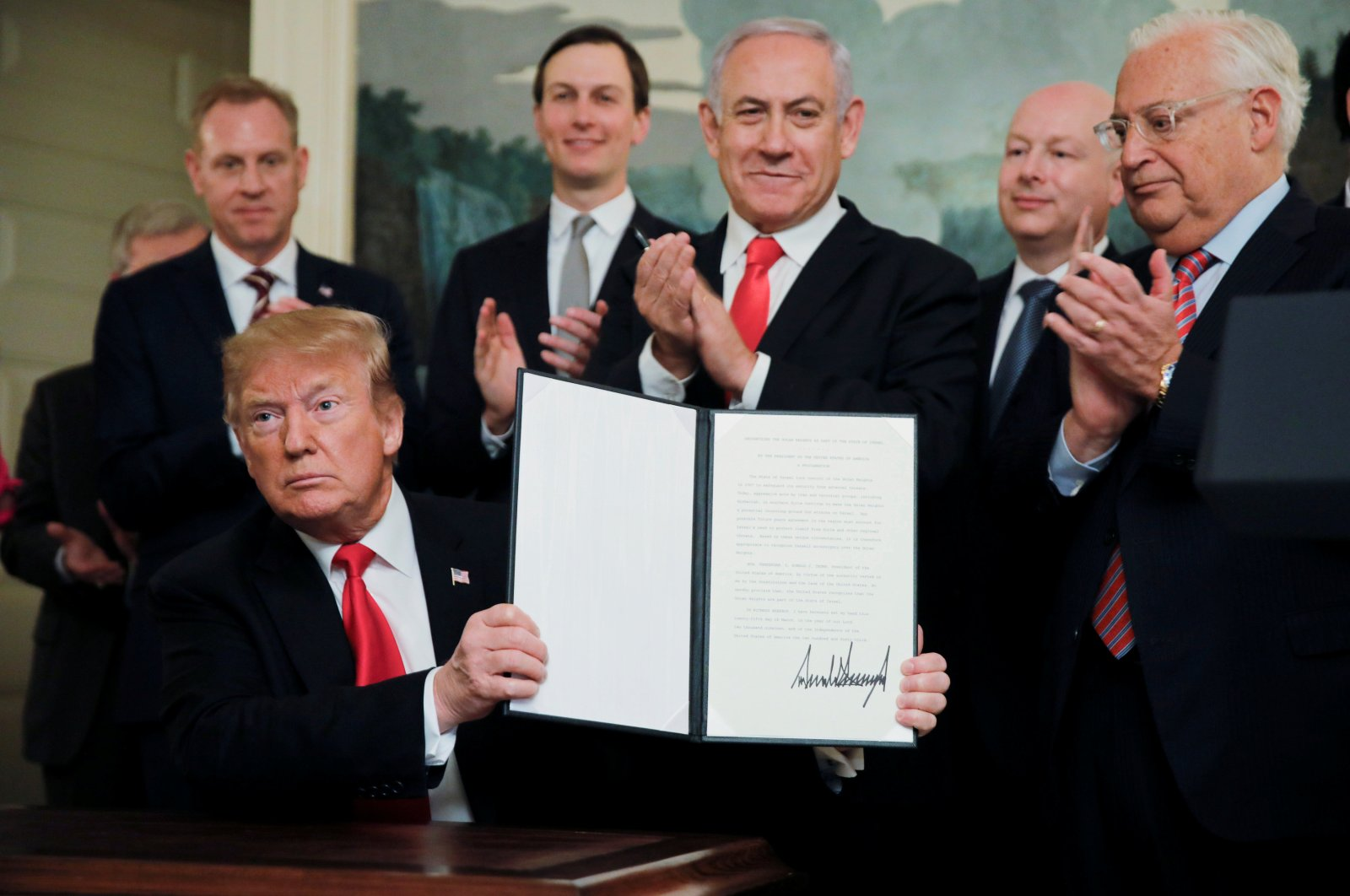 U.S. President Donald Trump holds a proclamation recognizing Israel's sovereignty over the Golan Heights as he is applauded by Israel's Prime Minister Benjamin Netanyahu and others during a ceremony at the White House in Washington, D.C., U.S., March 25, 2019. (Reuters Photo)