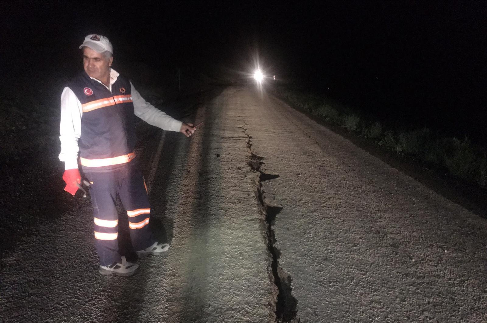 A Disaster and Emergency Management Authority (AFAD) employee stands by a crack that emerged in a road following a 5.7 magnitude earthquake, Bingöl, Turkey, June 14, 2020. (AA Photo)
