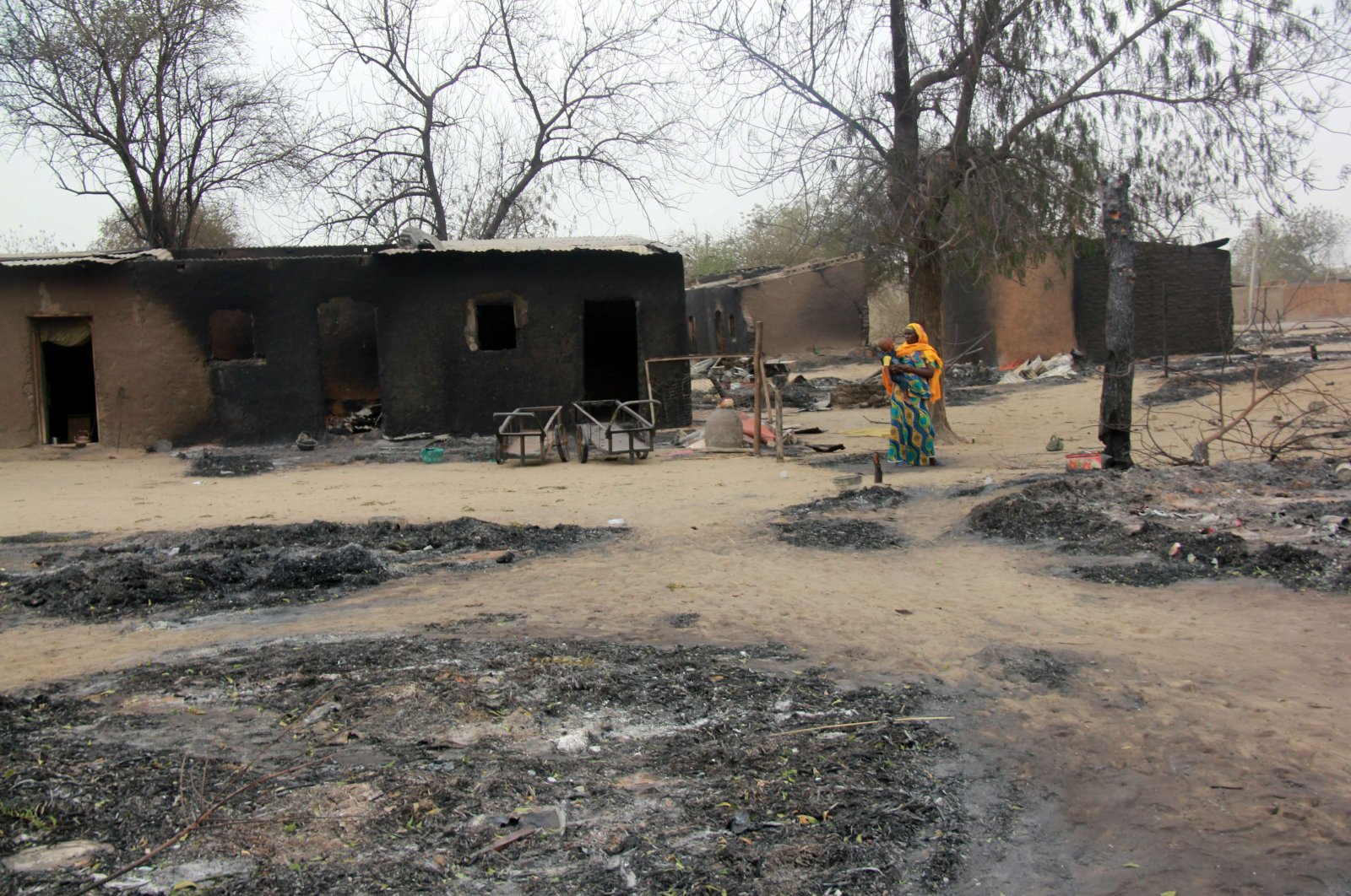 This file photo shows a woman walking past burnt houses after a two-day clash between officers of the Joint Task Force and members of Boko Haram, in Baga, Borno state, Nigeria, April 21, 2013. (AFP Photo)
