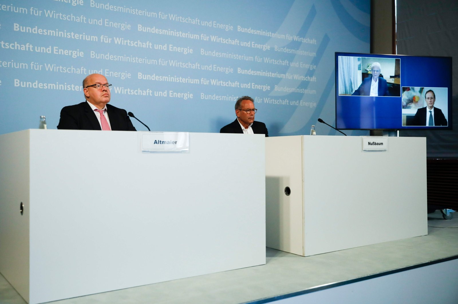 German Economy Minister Peter Altmaier (L), and state secretary at the economic ministry Ulrich Nussbaum (R) attend a news conference with CureVac main shareholder Dietmar Hopp (on the screen left) at the economy ministry in Berlin, June 15, 2020. (AFP Photo)