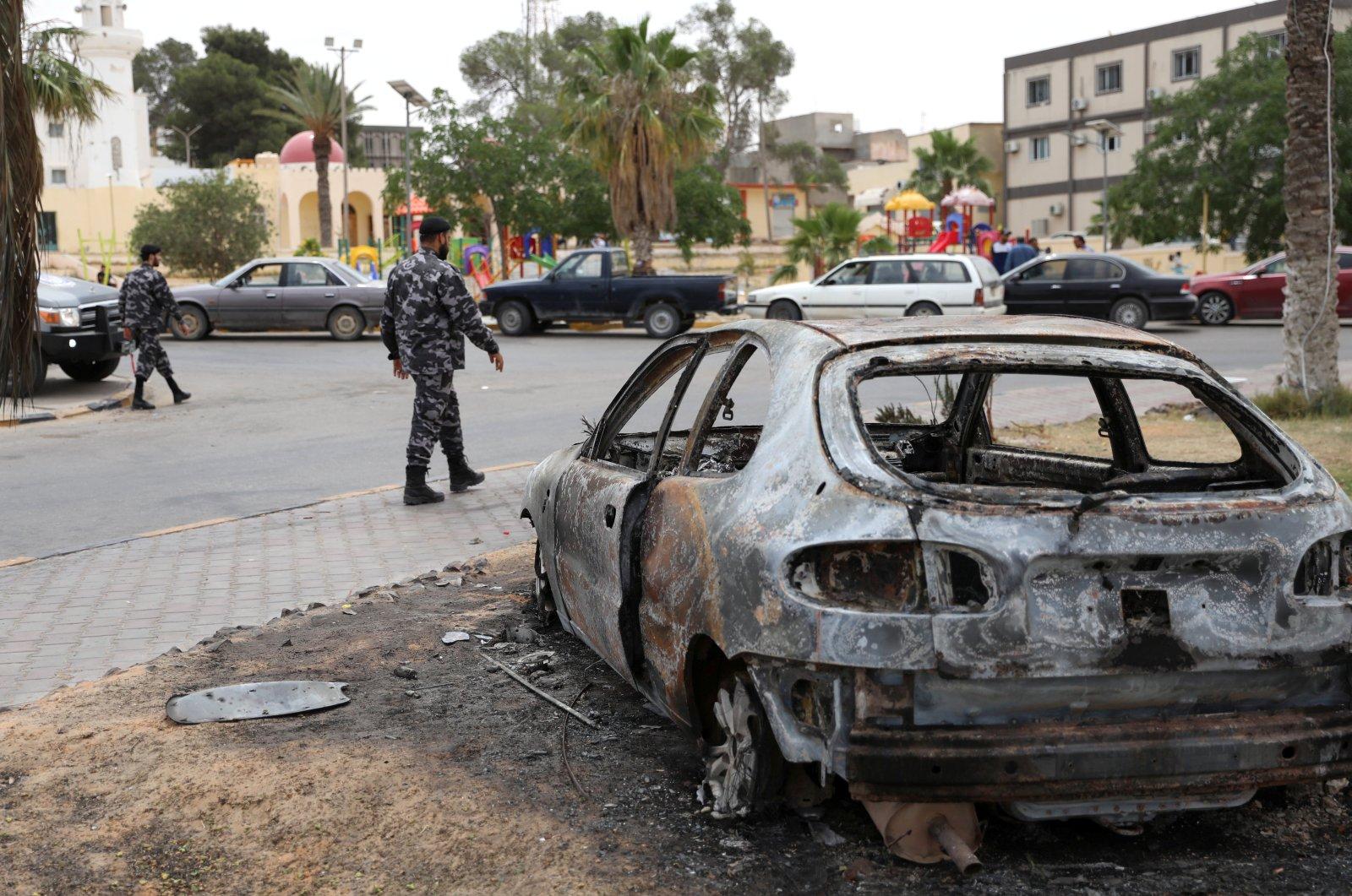 Libyan policemen walk near a damaged car during a security deployment in Tarhouna city, June 11, 2020. (REUTERS)