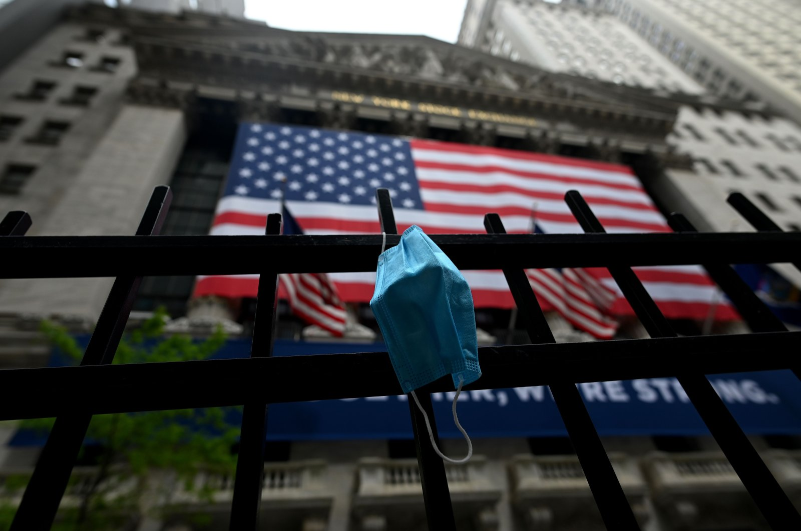 A face mask is seen in front of the New York Stock Exchange (NYSE), at Wall Street in New York City, New York, U.S., May 26, 2020. (AFP Photo)