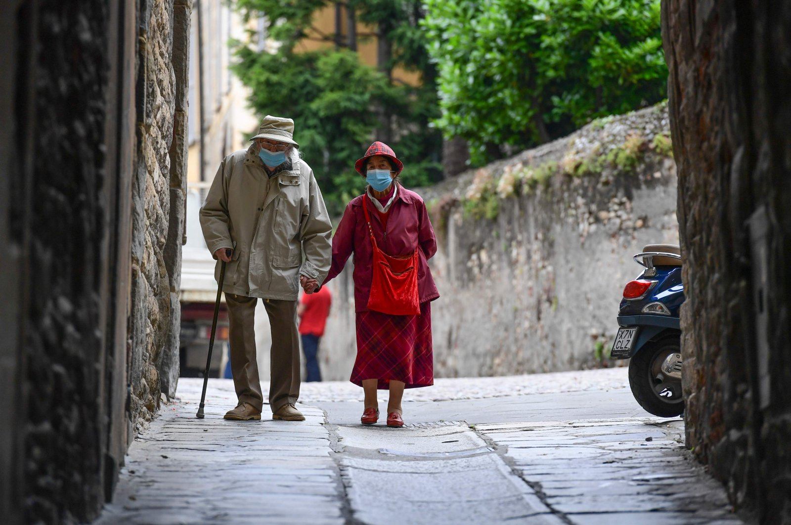 An elderly couple wearing face masks due to the coronavirus outbreak walk in a street in the upper city of Bergamo, Italy, June 10, 2020. (AFP Photo)