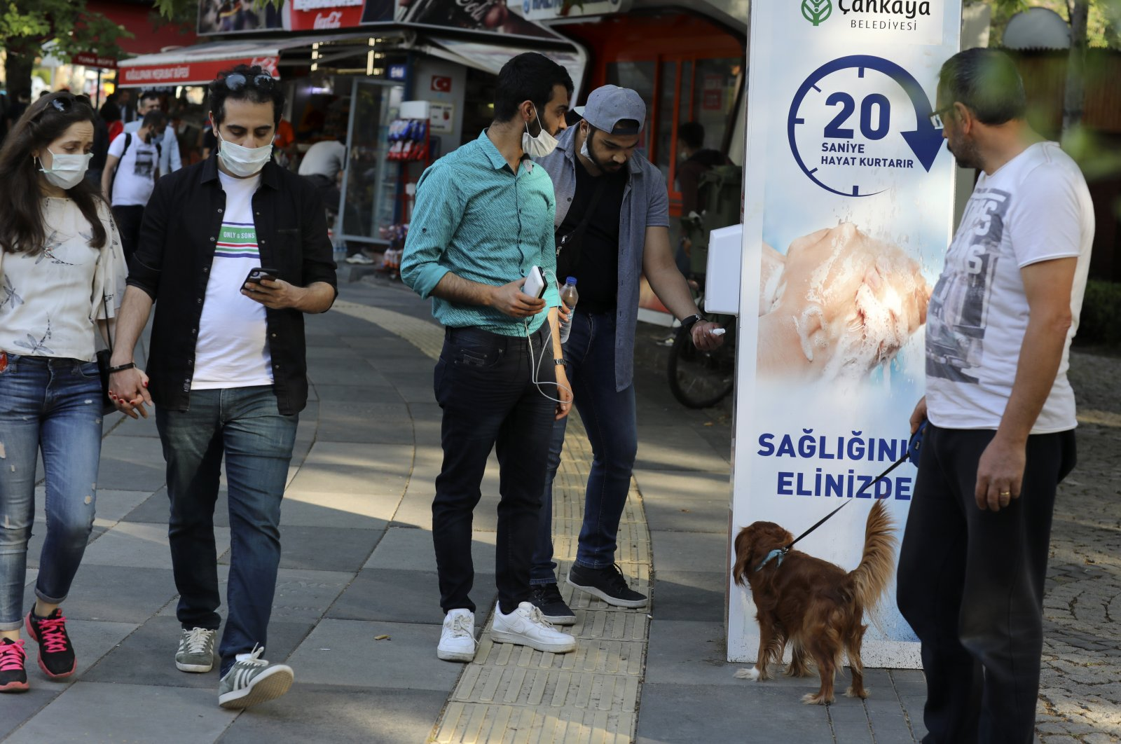 People wearing face masks use disinfectant at the entrance of a public garden, in Ankara, Turkey, June 14, 2020. (AP Photo)