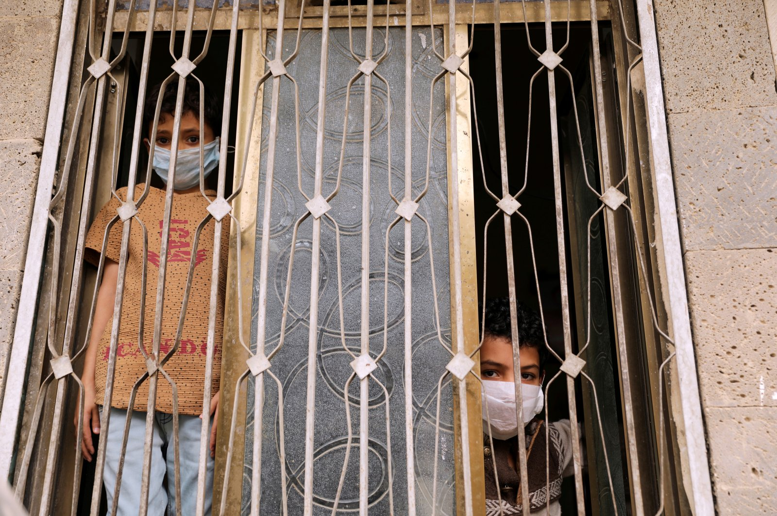 Children wearing protective masks look from behind a window, Sanaa, Yemen, May 6, 2020. (REUTERS Photo)