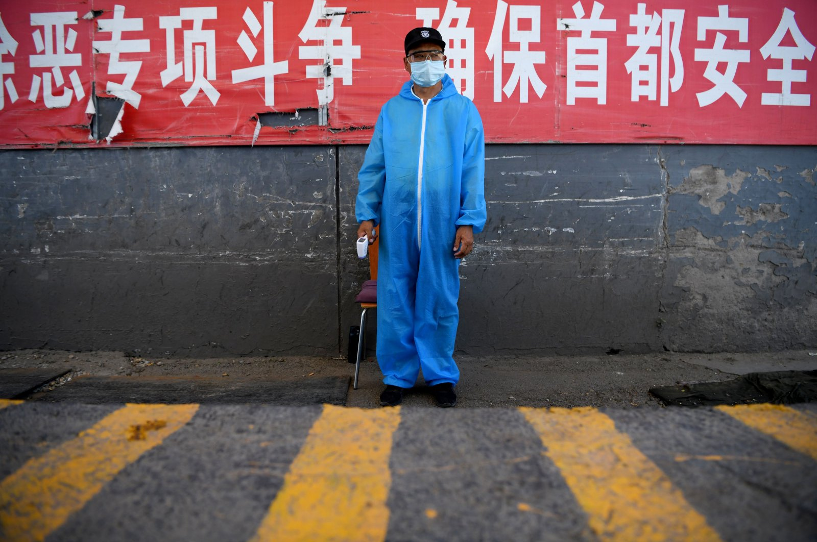 A security guard wearing a protective mask and suit stands at a checkpoint at the Xinfadi market, Beijing, June 14, 2020. (AFP Photo)