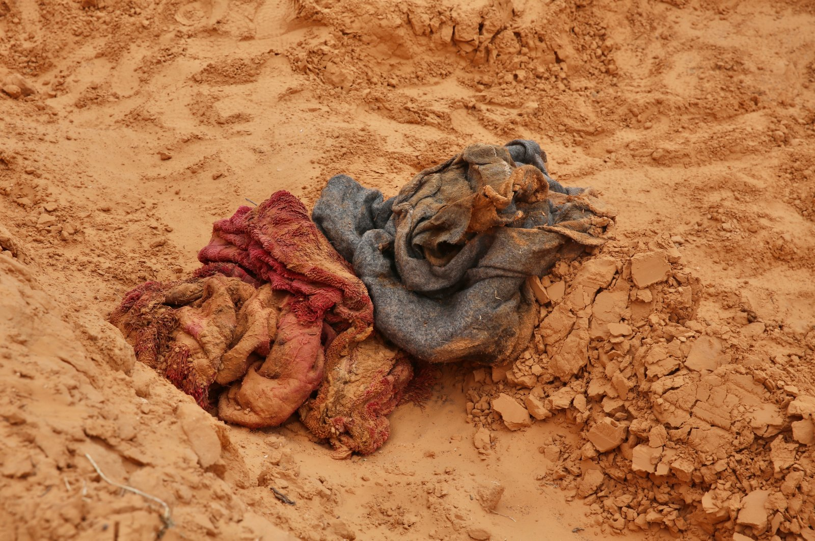 Scraps of clothing were scattered around the site near mass graves covered with fresh soil in Libya's Tarhuna province, June 12, 2020. (AA Photo)
