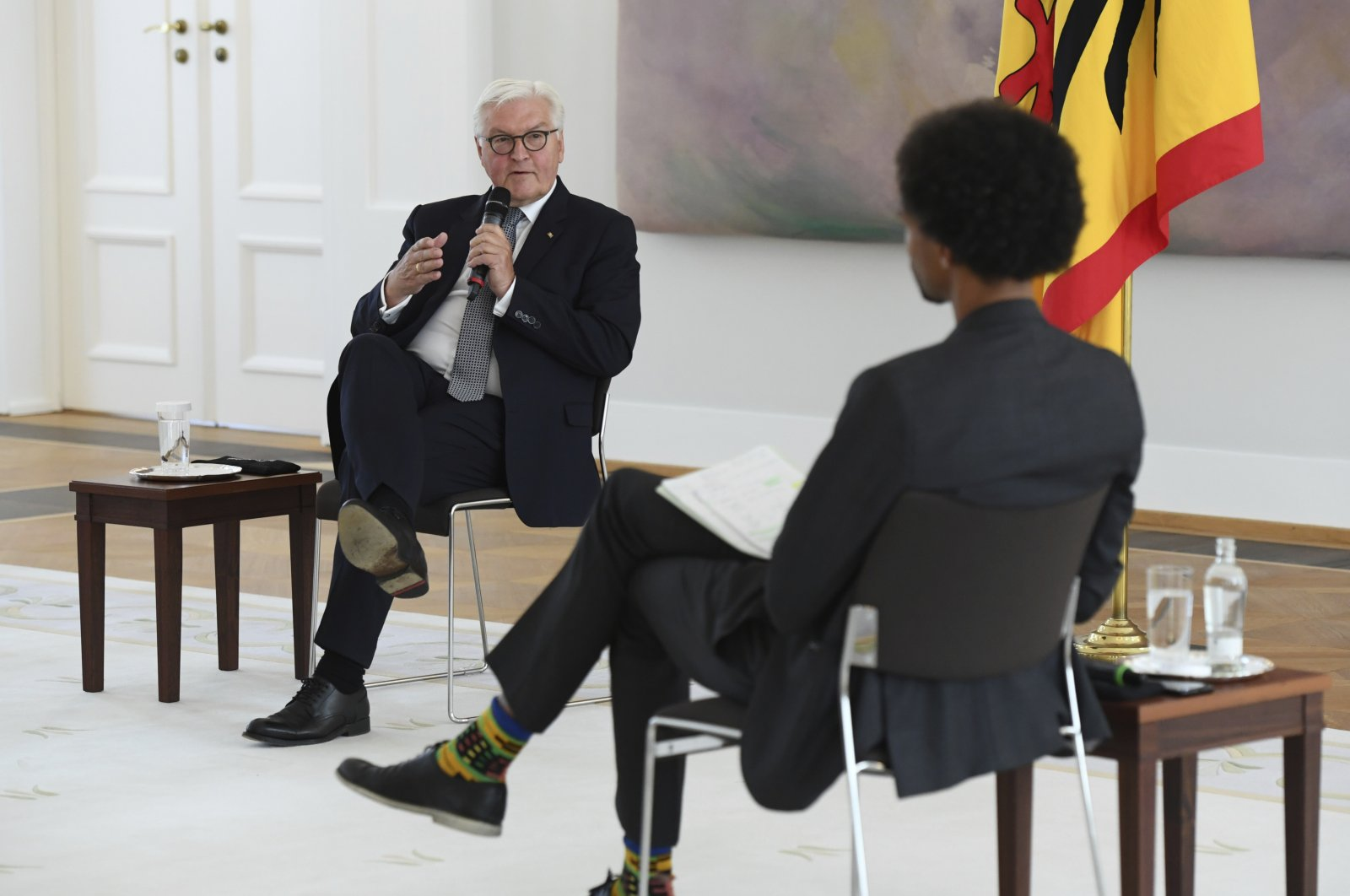 """Federal President Frank-Walter Steinmeier (L) talks to his guest Daniel Gyamerah, head of the """"Advocating for Inclusion"""" department of the Berlin-based think tank """"Citizens for Europe,"""" during a discussion round on experiences of racism and discrimination at Bellevue Palace, Berlin, June 16, 2020. (AP Photo)"""