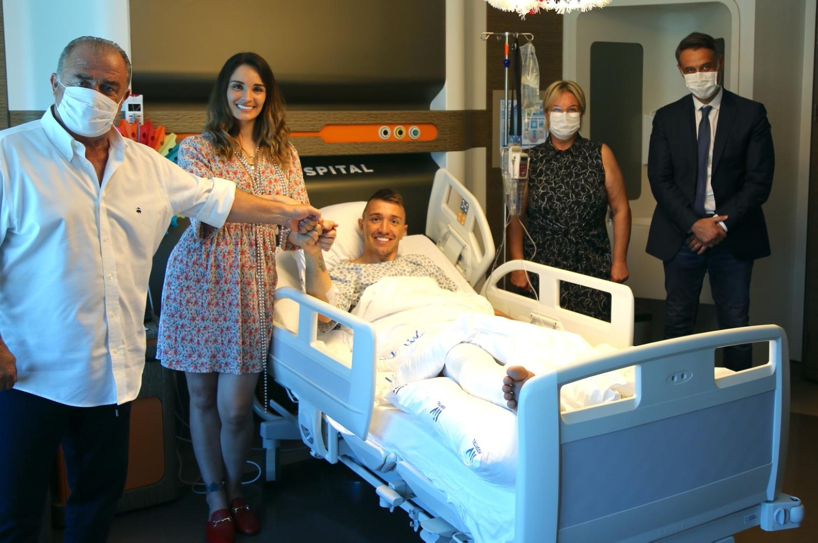 Fernando Muslera (C) poses with his wife Patricia Callero (L) and Galatasaray Coach Fatih Terim (2nd L) after his surgery in Istanbul, Turkey, June 16, 2020. (DHA Photo)