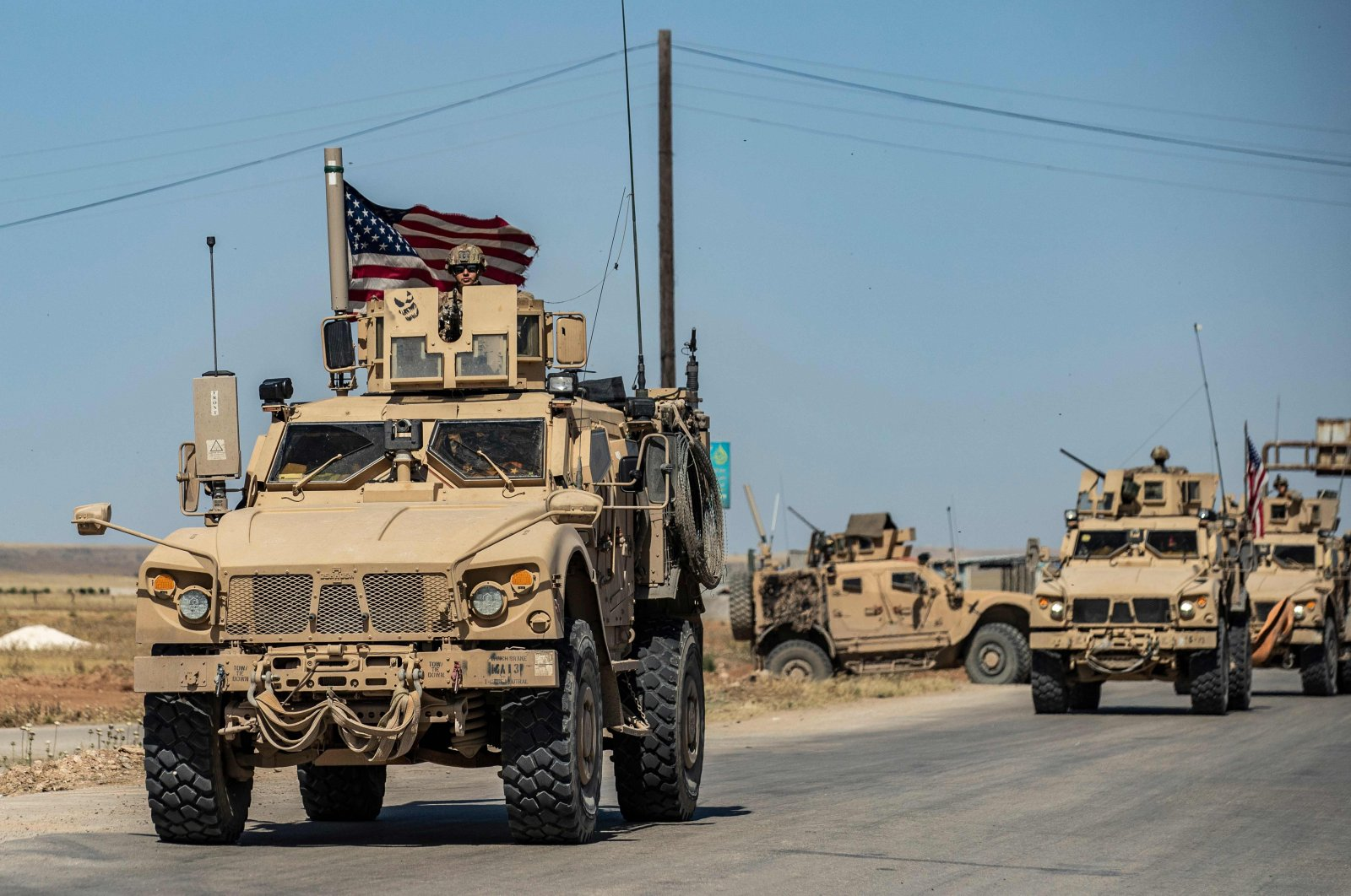 U.S. military vehicles patrol along the M4 highway near Tal Tamr, northeastern Syria, May 20, 2020. (AFP Photo)